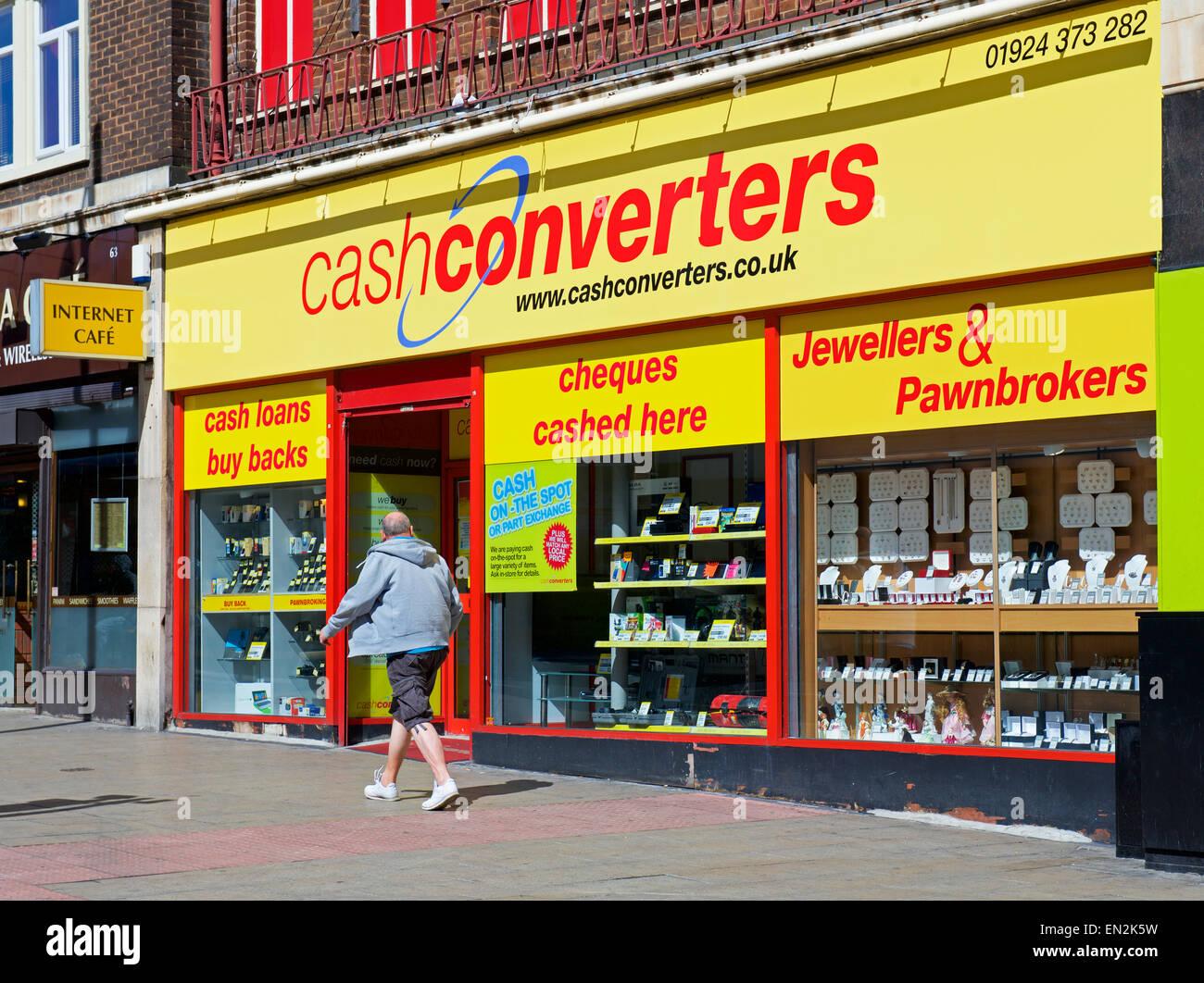 Man walking past branch of Cash Converters, England UK - Stock Image