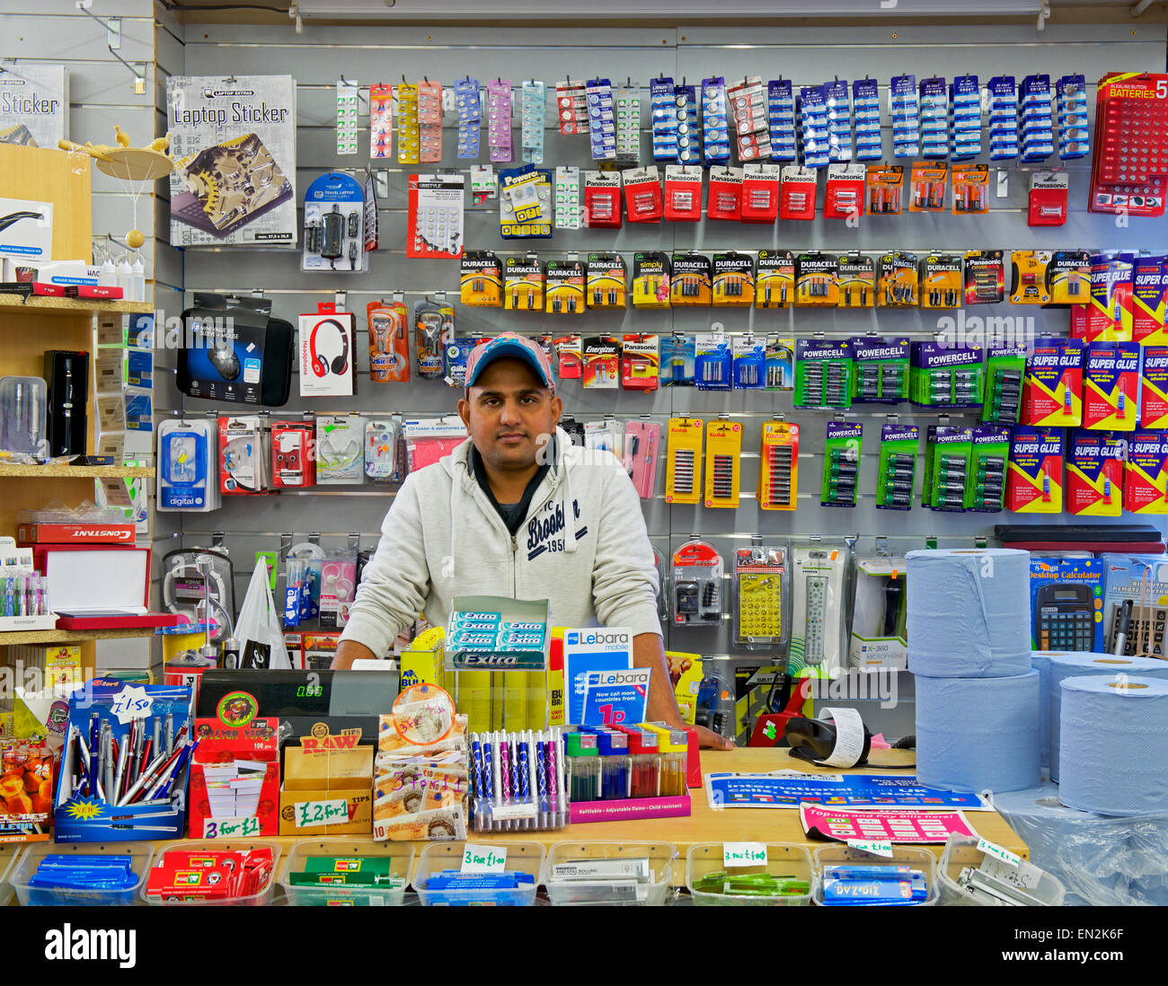 Man behind counter of pound shop in Wakefield, West Yorkshire, England UK - Stock Image