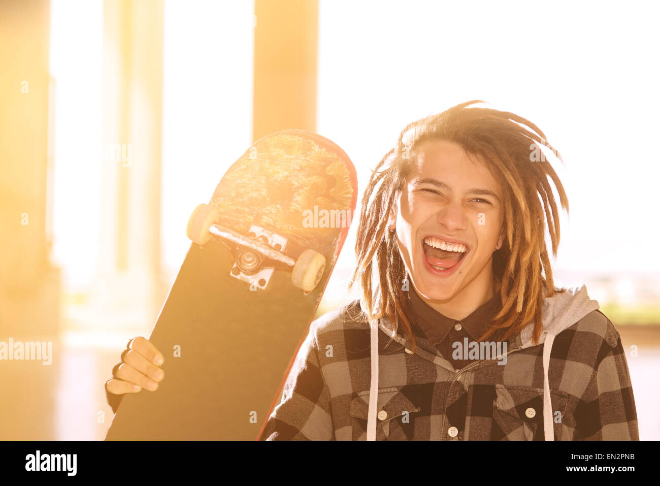 portrait of young guy  with skateboard and rasta hair in a lifestyle concept warm filter applied - Stock Image