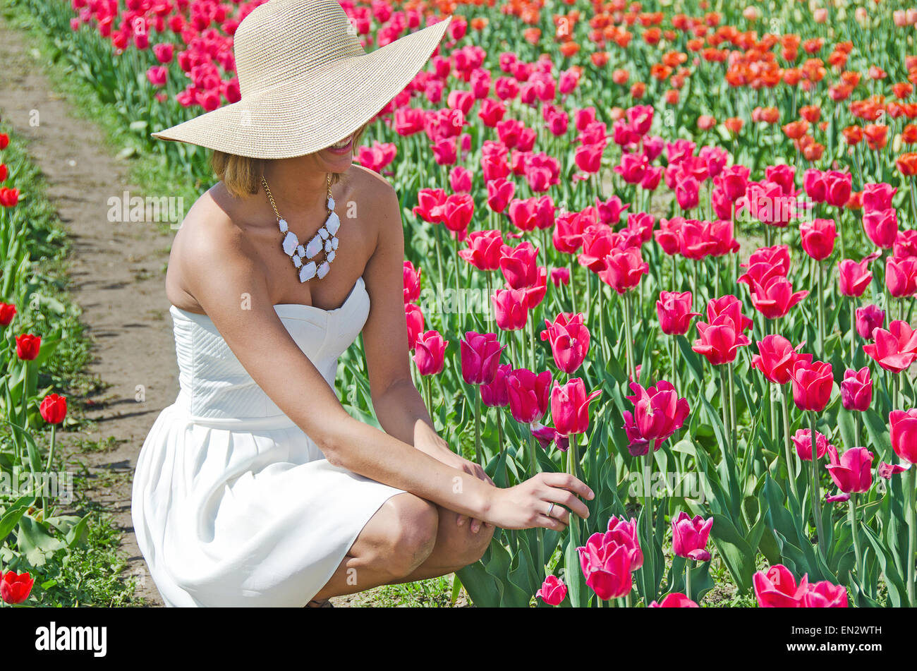 Pretty woman with fashion hat and strapless white sundress in a spring tulip garden. - Stock Image