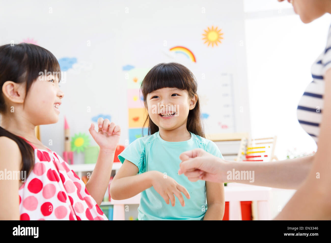 The kindergarten teacher and the girl in the finger guessing game - Stock Image