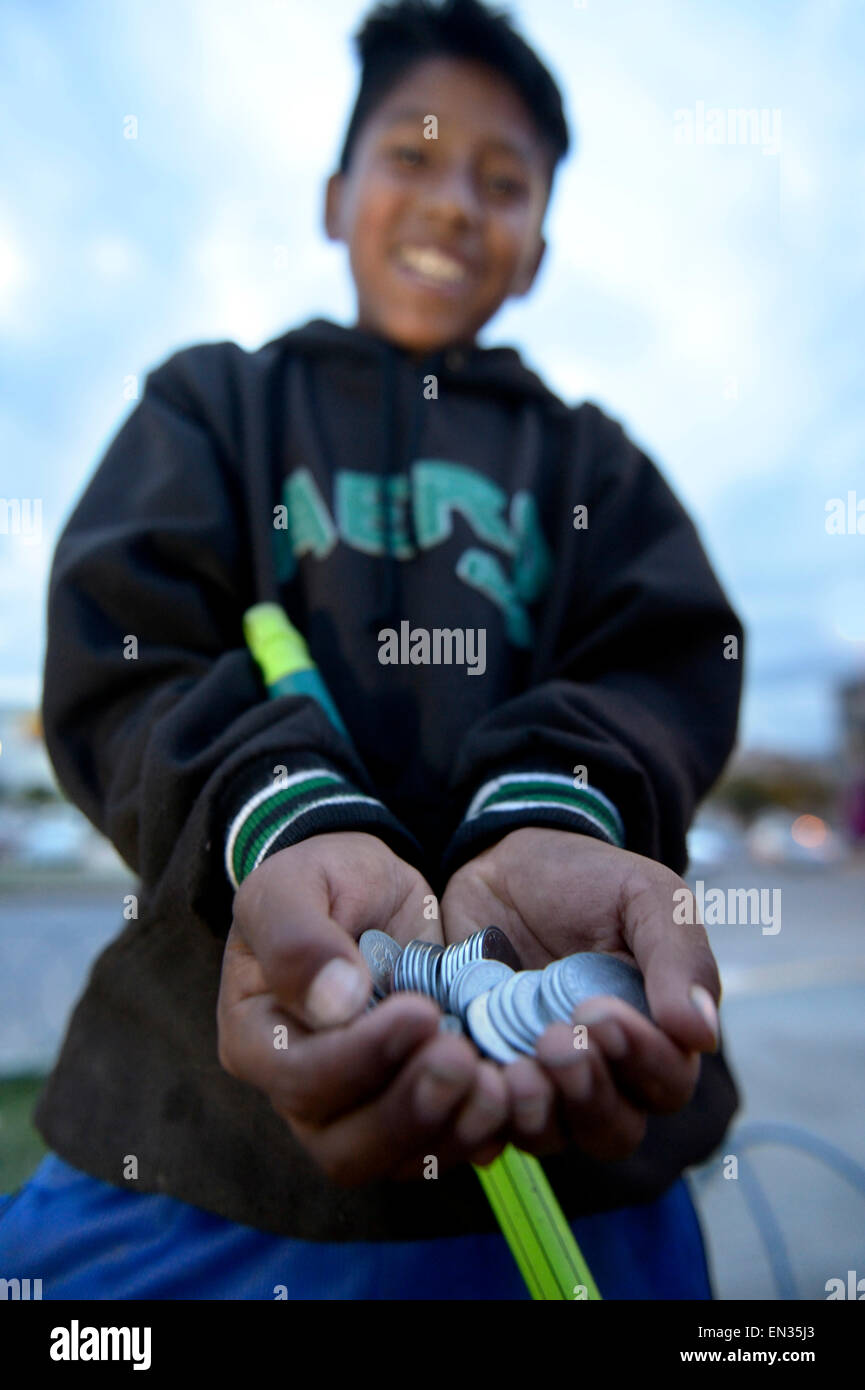 Street child with money earned from cleaning windshields, Cochabamba, Bolivia - Stock Image