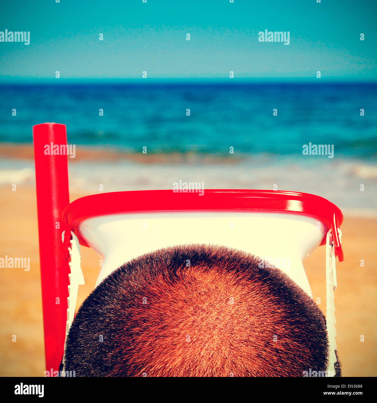 picture from the back of a man wearing a diving mask and a snorkel on the beach, with a retro effect - Stock Image
