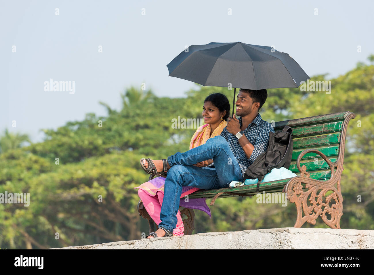 Young couple with a parasol sitting on a park bench, Fort Kochi, Kerala, India - Stock Image