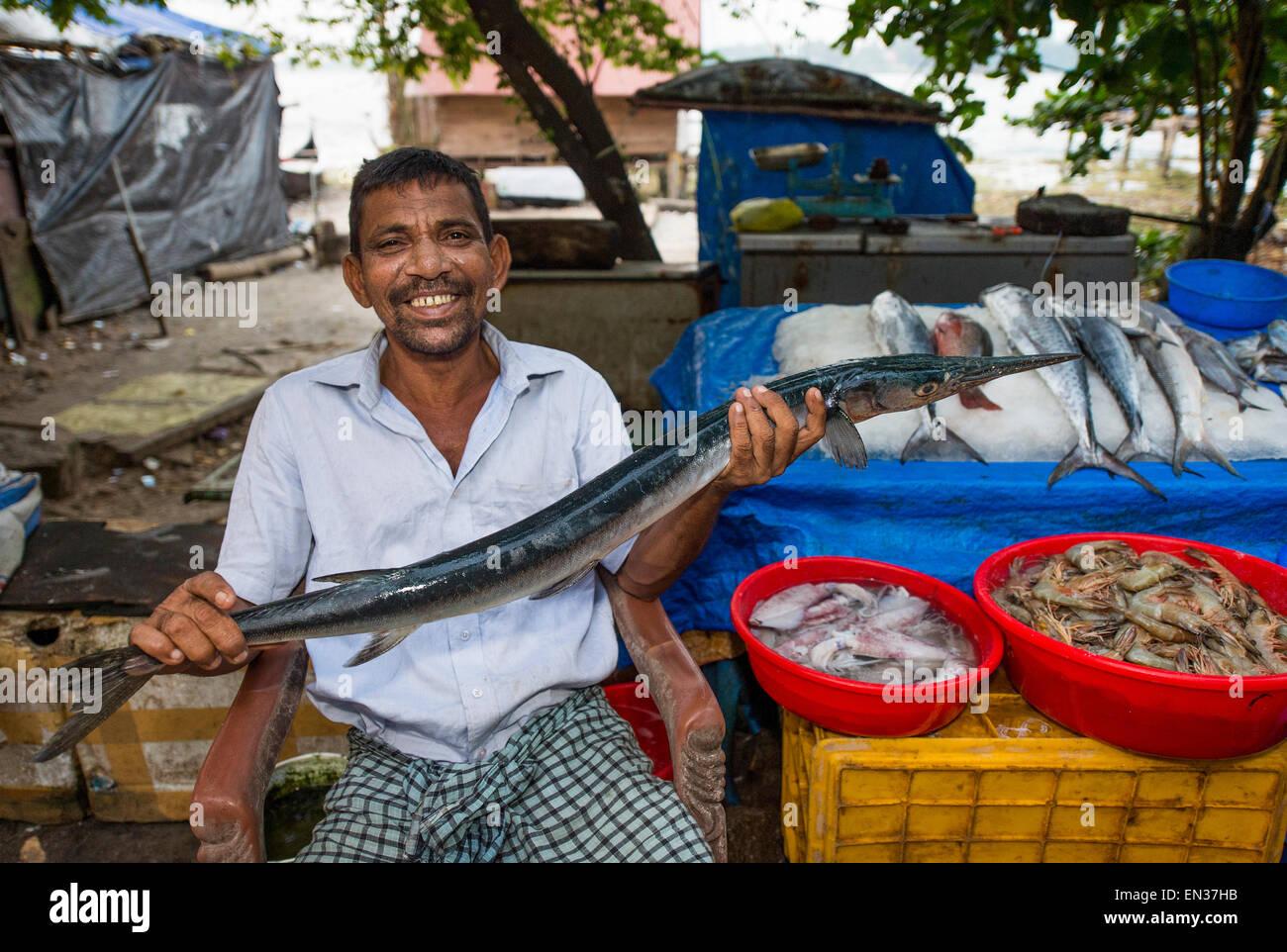 Fish seller holding a Freshwater Garfish (Xenentodon cancila), Fort Kochi, Kerala, India - Stock Image