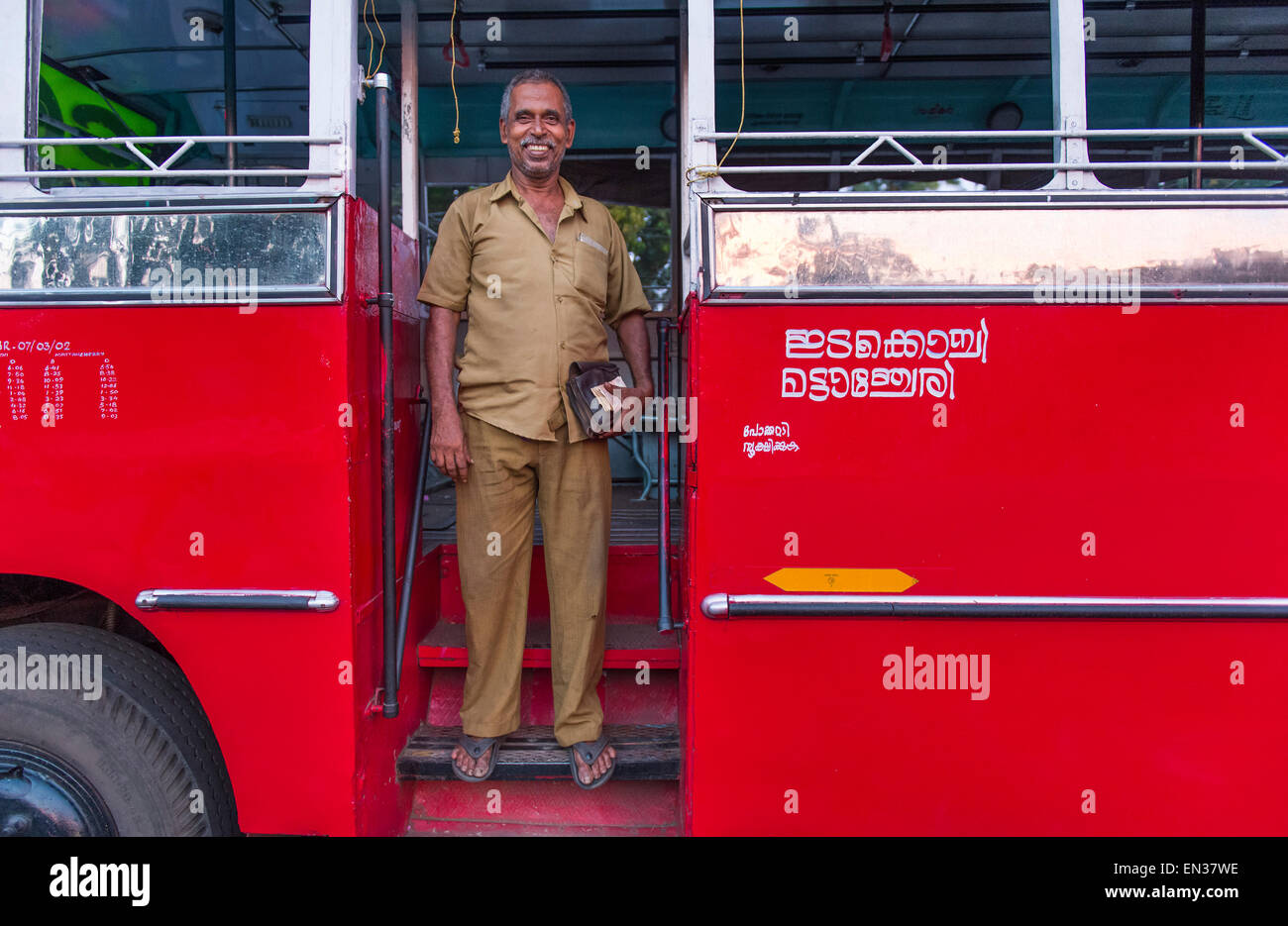 Bus driver in front of a red bus, Kerala, India - Stock Image