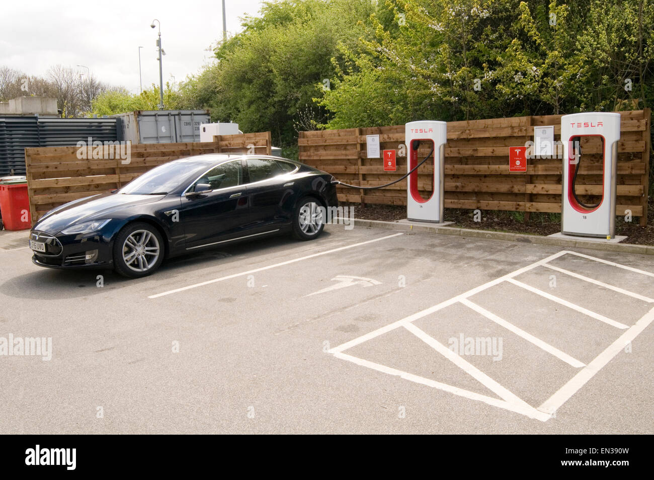 tesla electric car cars supercharger plugged in charging up on the m62 in leeds - Stock Image