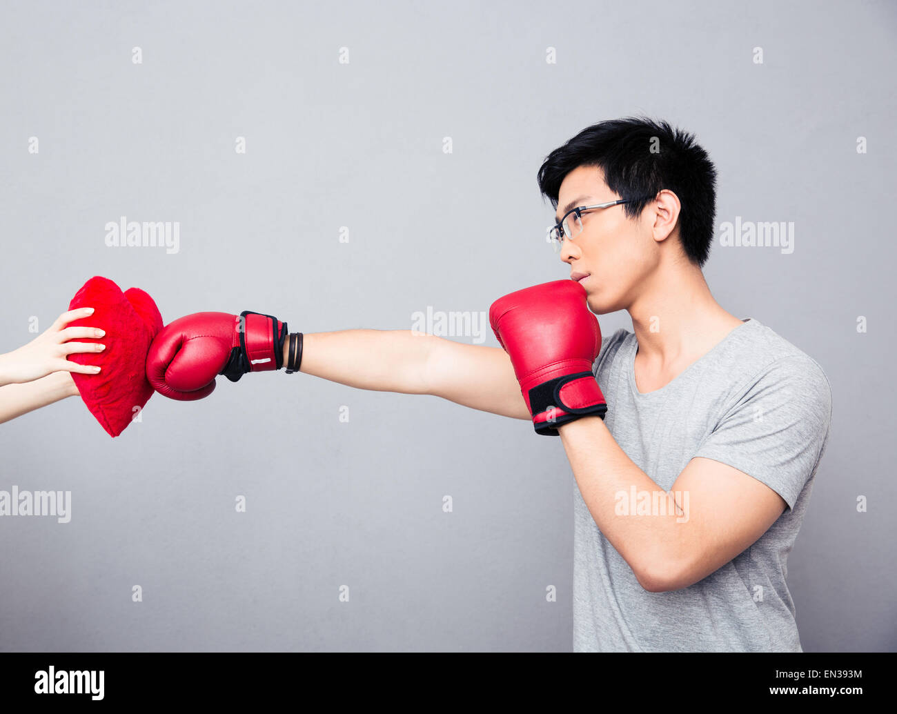 Concept image of a man in boxing gloves hitting at heart over gray background Stock Photo