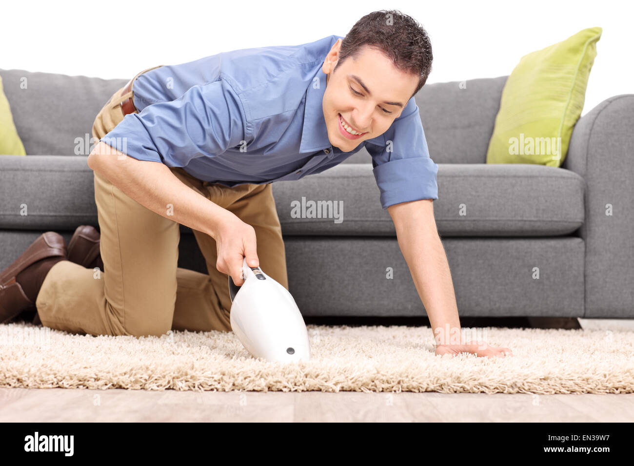 Young joyful man vacuuming a carpet with a handheld vacuum cleaner isolated on white background Stock Photo