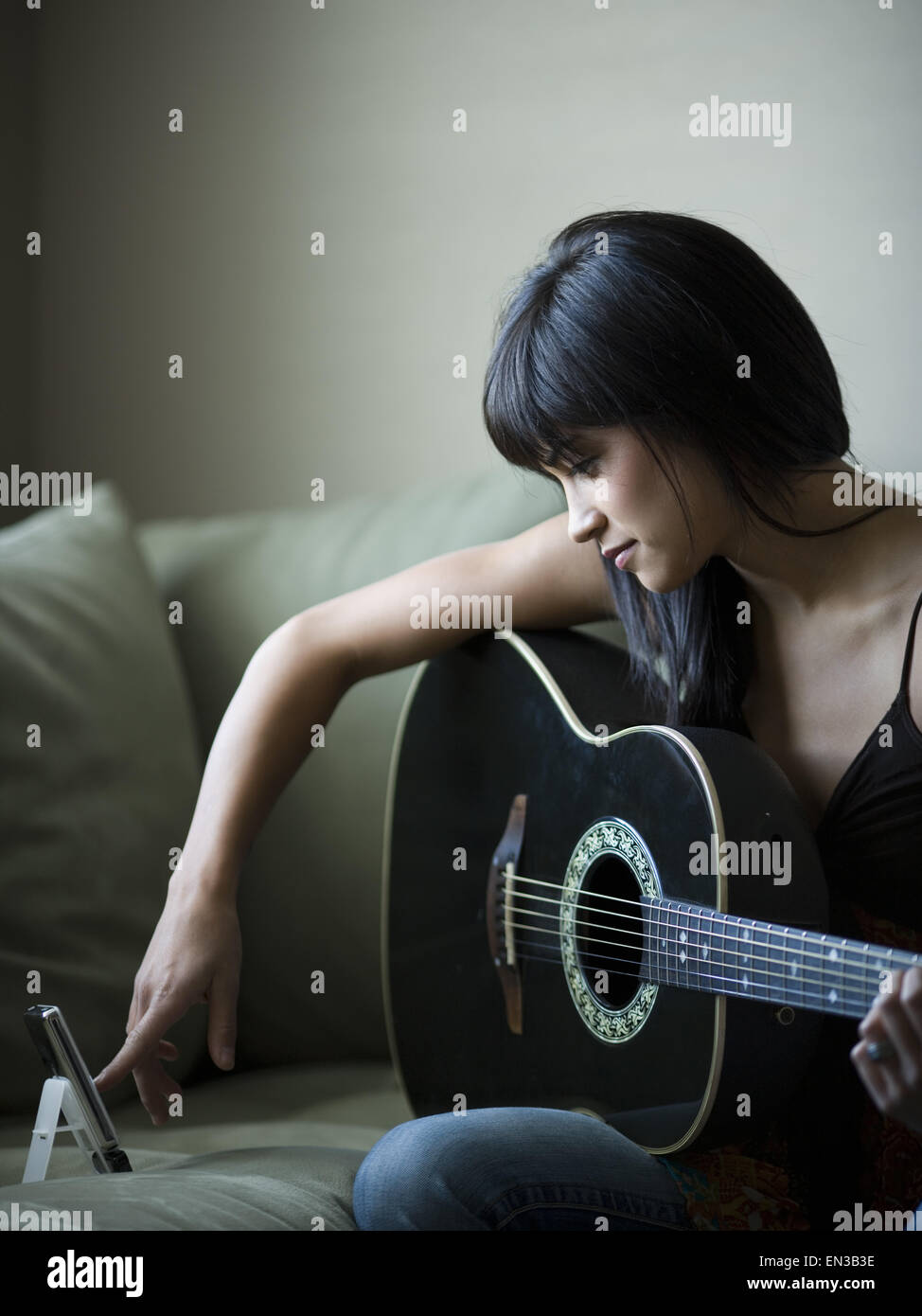 Woman tuning guitar with metronome - Stock Image