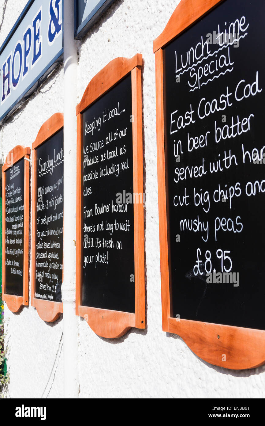 Restaurant food information and menu blackboards on the exterior wall of the Hope and Anchor hotel, Alnmouth, Northumberland. - Stock Image