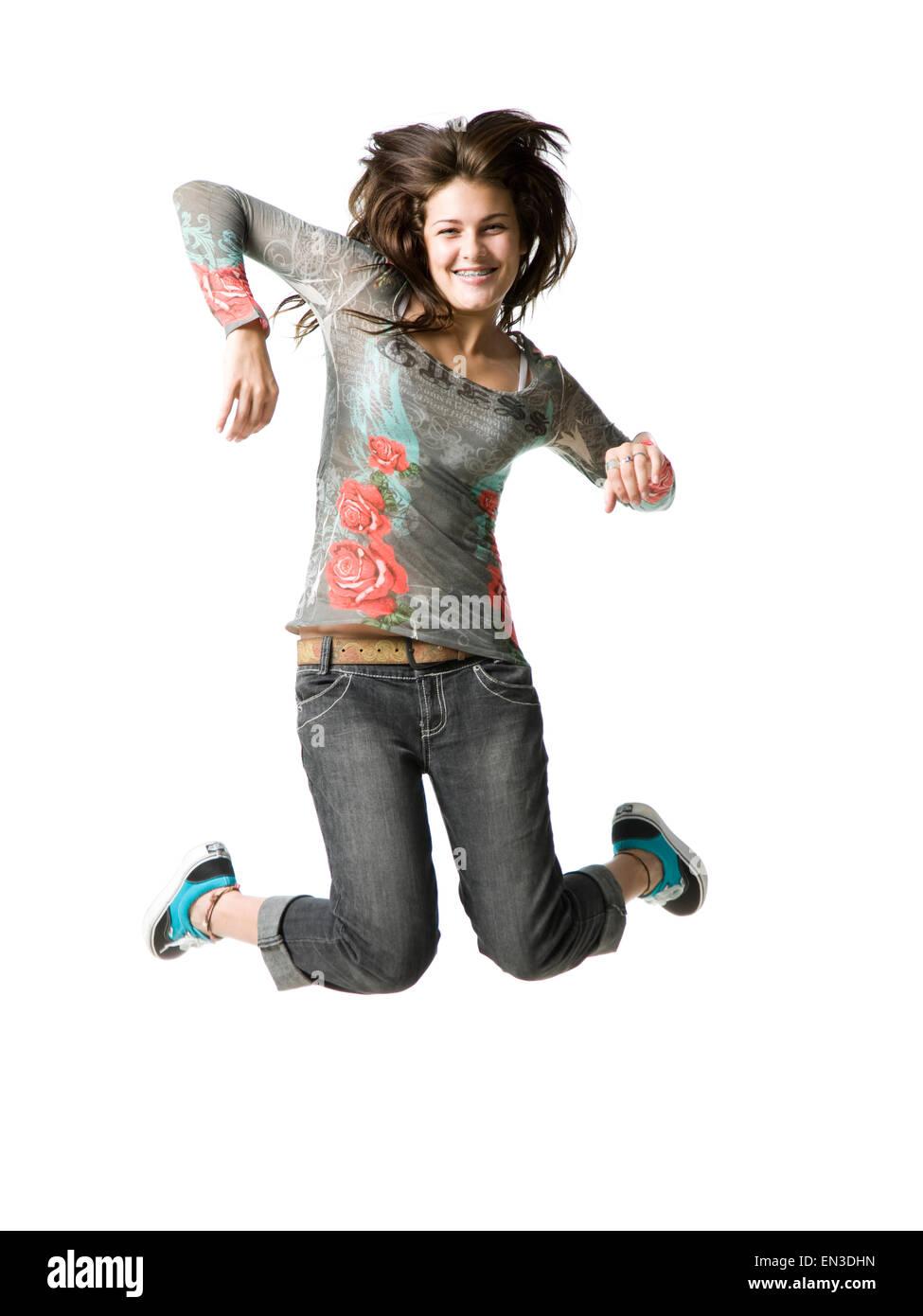 Studio portrait of teenage girl (16-17) jumping, smiling - Stock Image
