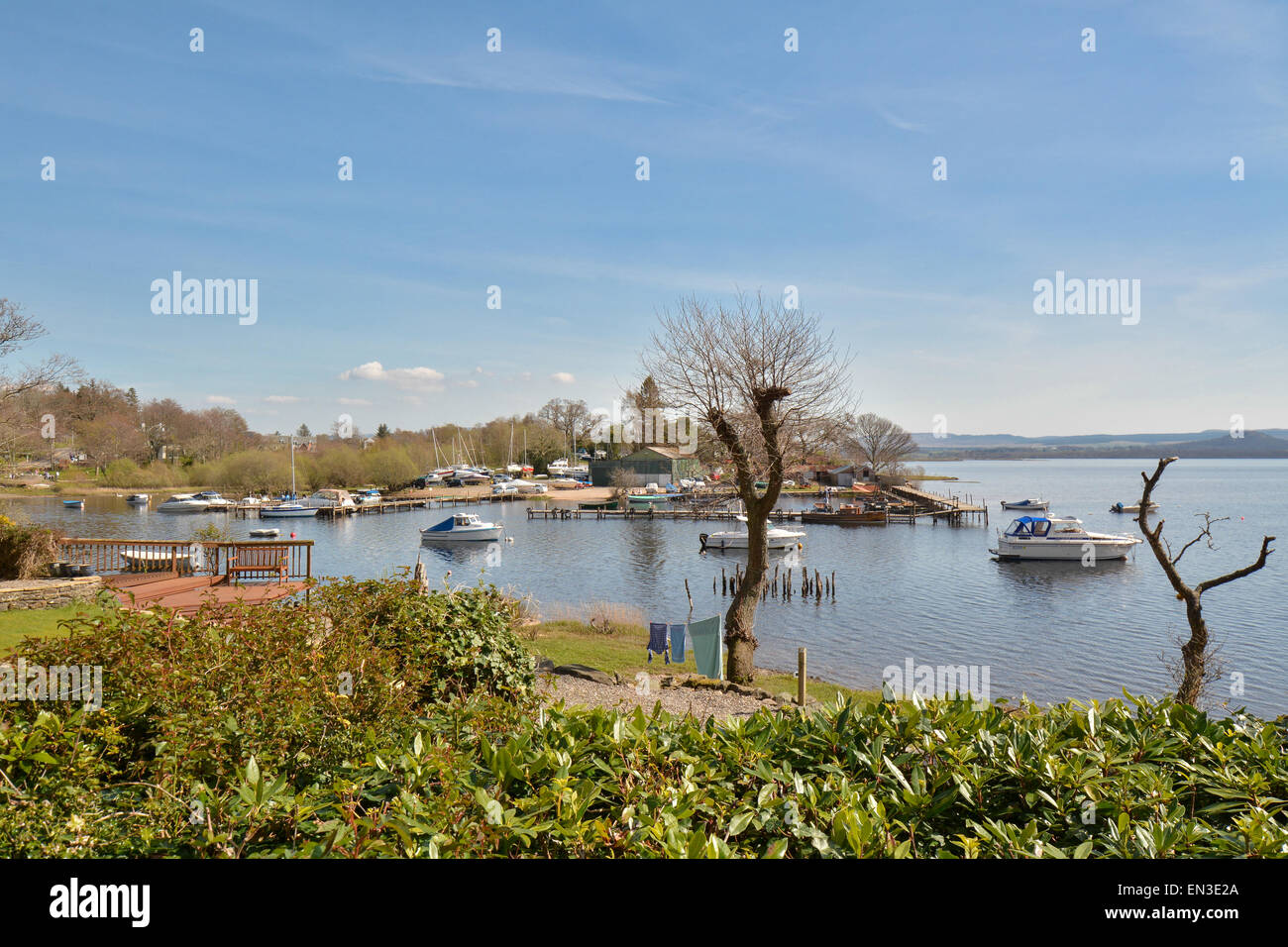 BALMAHA, LOCH LOMOND, SCOTLAND, UK - 22 APRIL 2015: Balmaha boatyard and marina on still, warm spring day - Stock Image