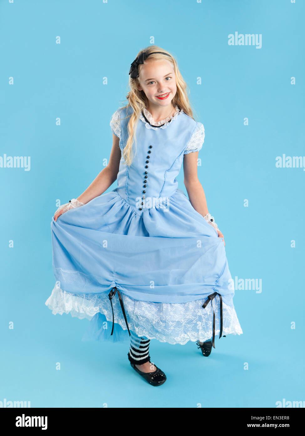 Portrait of girl (10-11) in Alice in Wonderland costume for Halloween - Stock Image