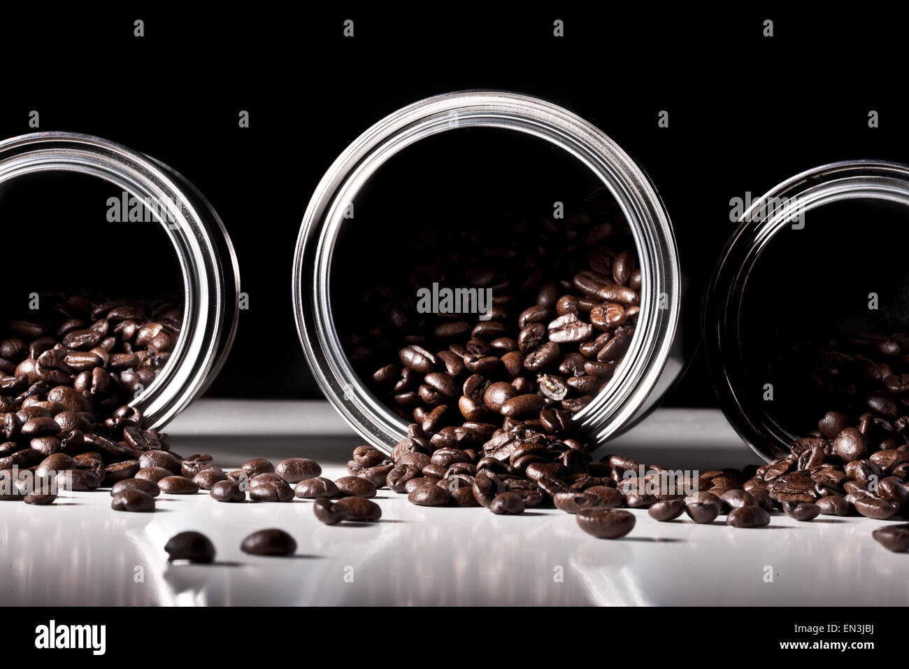 Studio shot of coffee beans spilling from tins - Stock Image