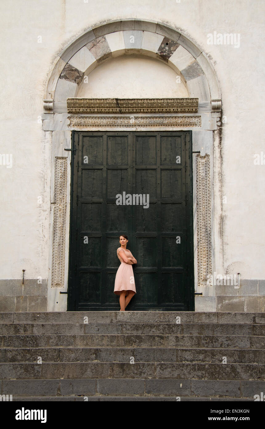 Italy, Ravello, Woman standing in front of closed doors - Stock Image