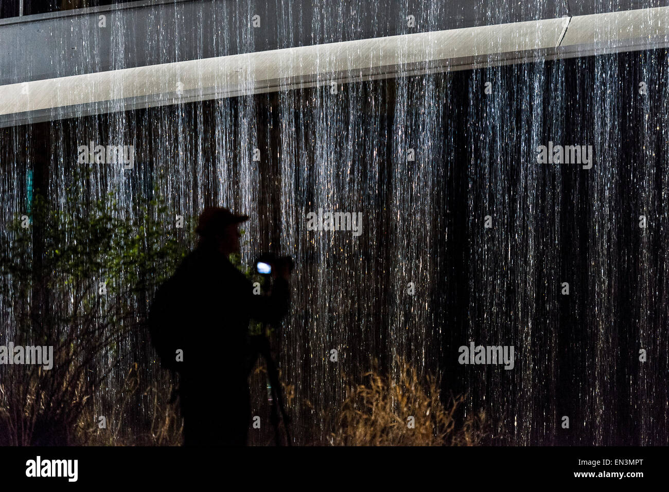 A man takes pictures of a bridge with a water curtain flowing down during a test-run of the art installation 'Wasser - Stock Image