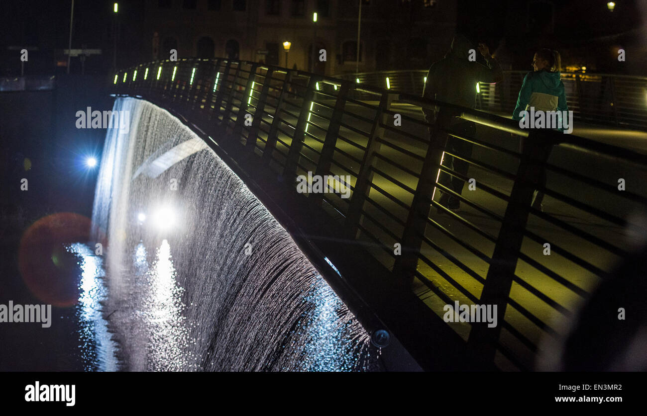 A man walks across a bridge with a water curtain flowing down aduring a test-run of the art installation 'Wasser - Stock Image
