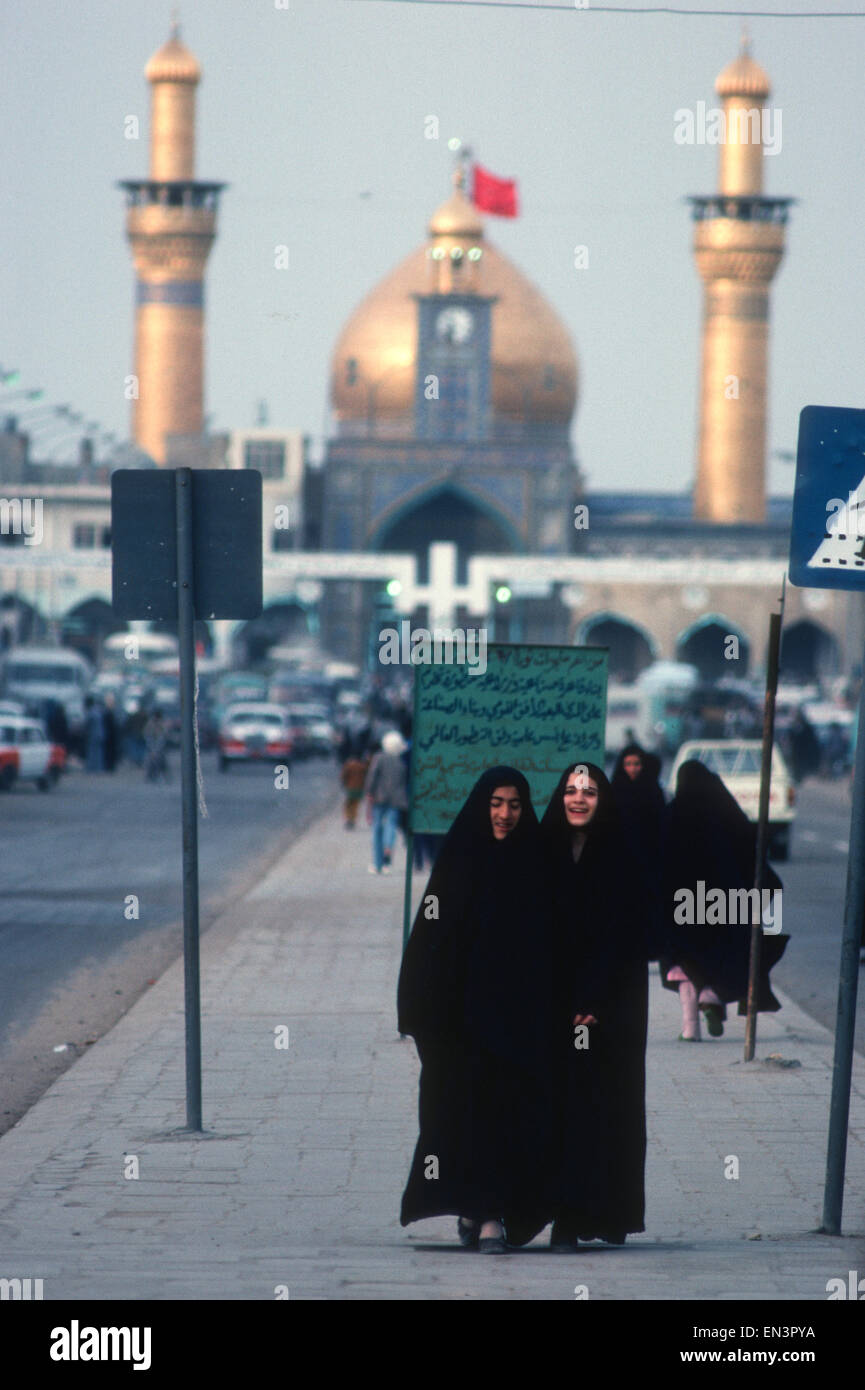 iraqi women walk in street in Kerbala in front of Shia shrine of Al Hussein Ibn Ali mosque, Iraq - Stock Image