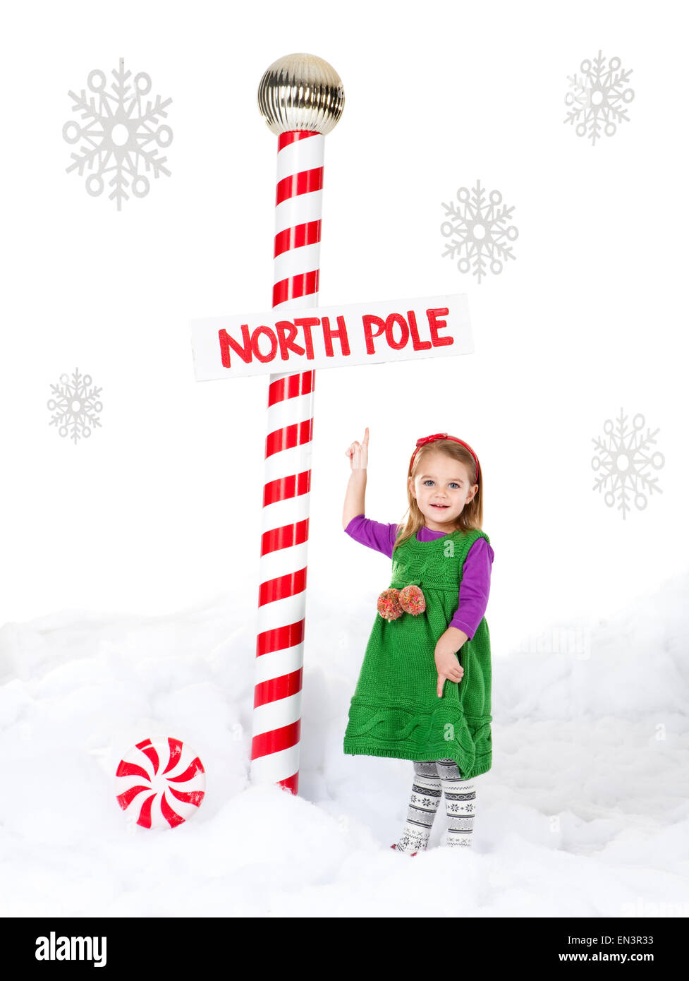 Little girl (18-23 months) standing next to North Pole sign - Stock Image