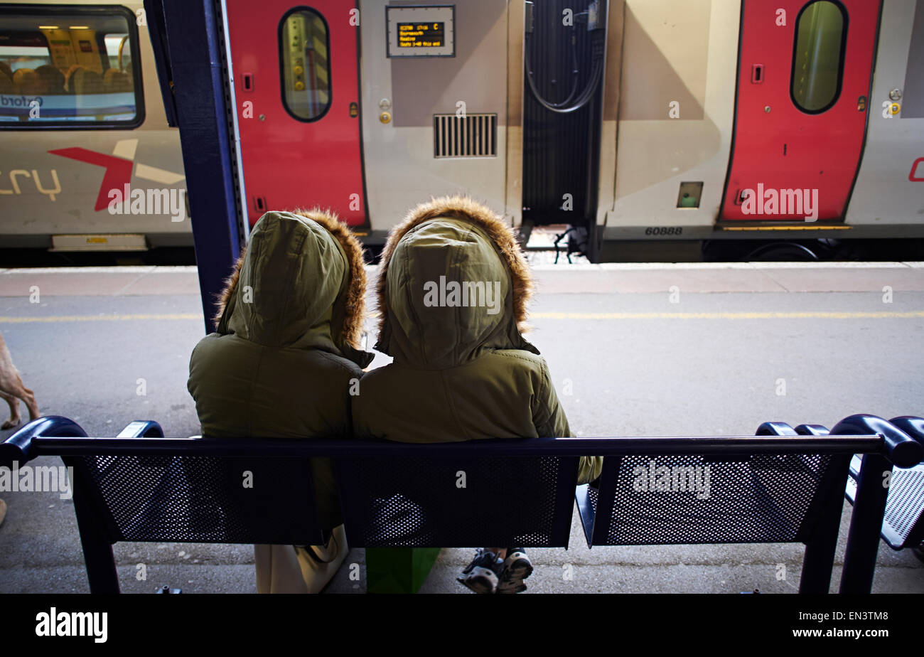 Identical twin girls in same parker coat waiting for train at Oxford Station. - Stock Image