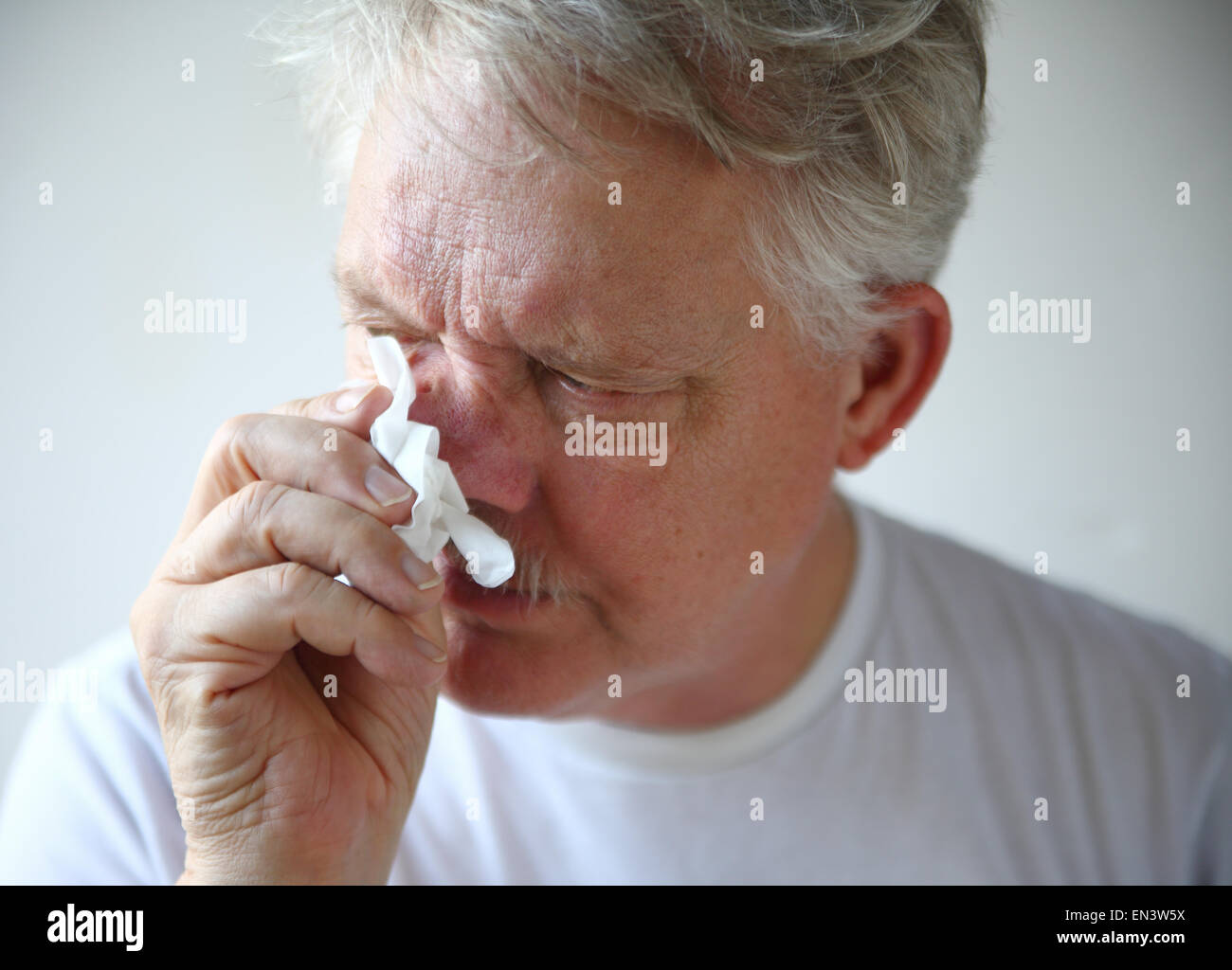 A man with the flu or a cold wipes his runny nose. - Stock Image