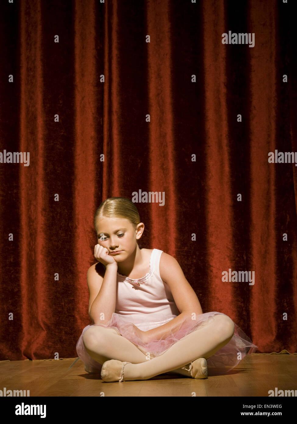 Ballerina girl sitting on stage sulking - Stock Image