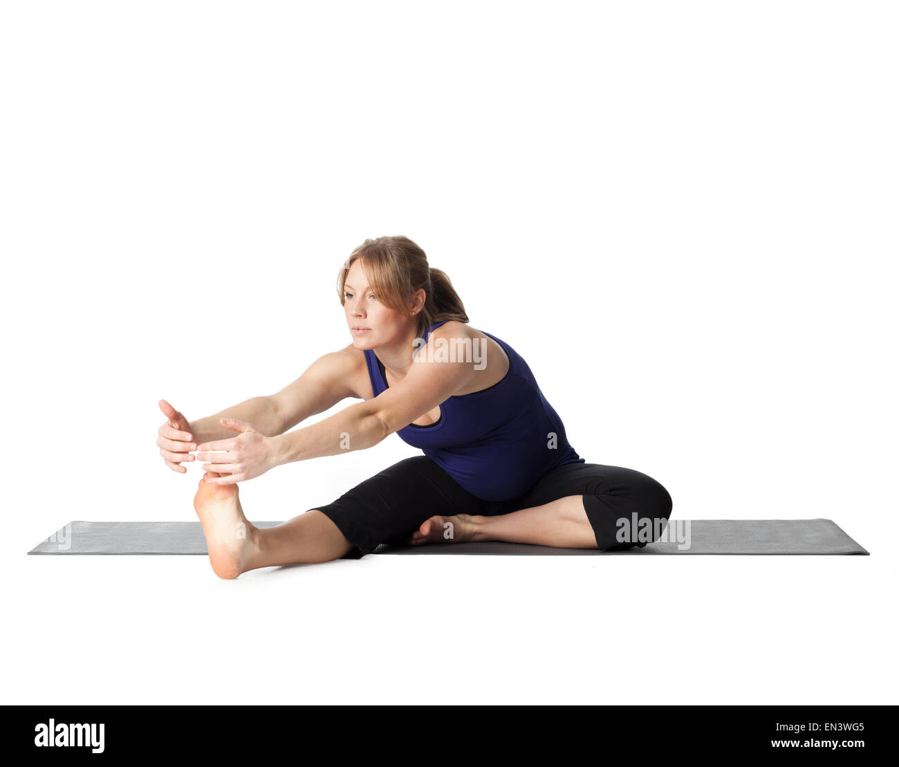 Young pregnant woman practicing yoga,  studio shot - Stock Image