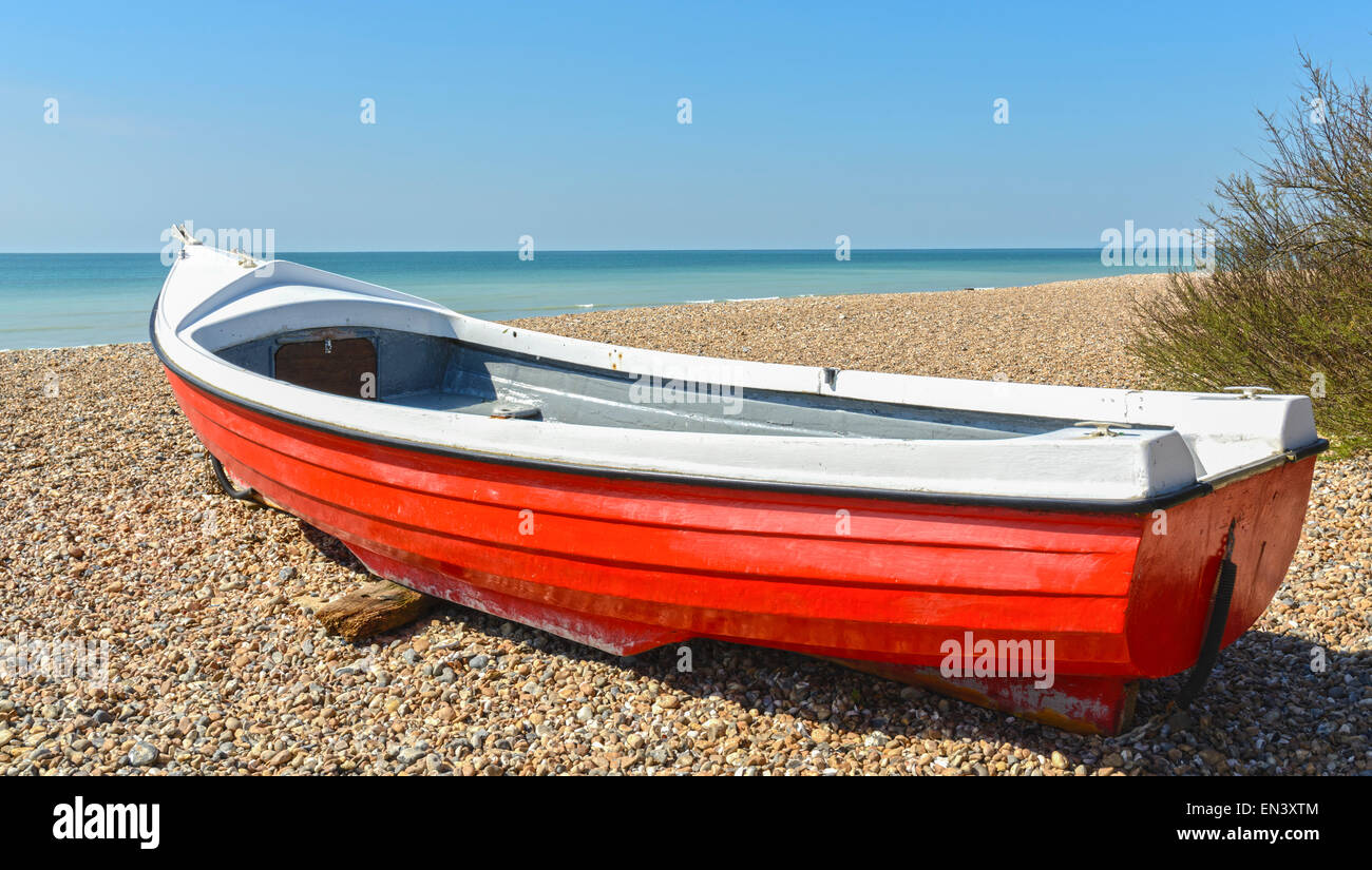 Small wooden boat on a shingle beach by the sea. Stock Photo
