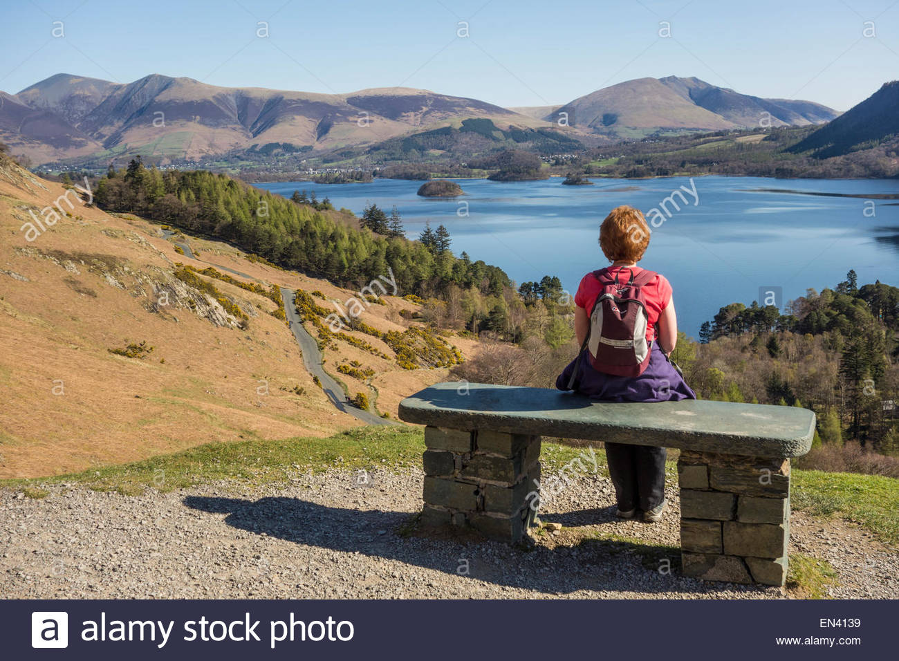 A walker resting at a viewpoint on the slopes below Catbells, with Derwentwater and the distant hills of Skiddaw - Stock Image