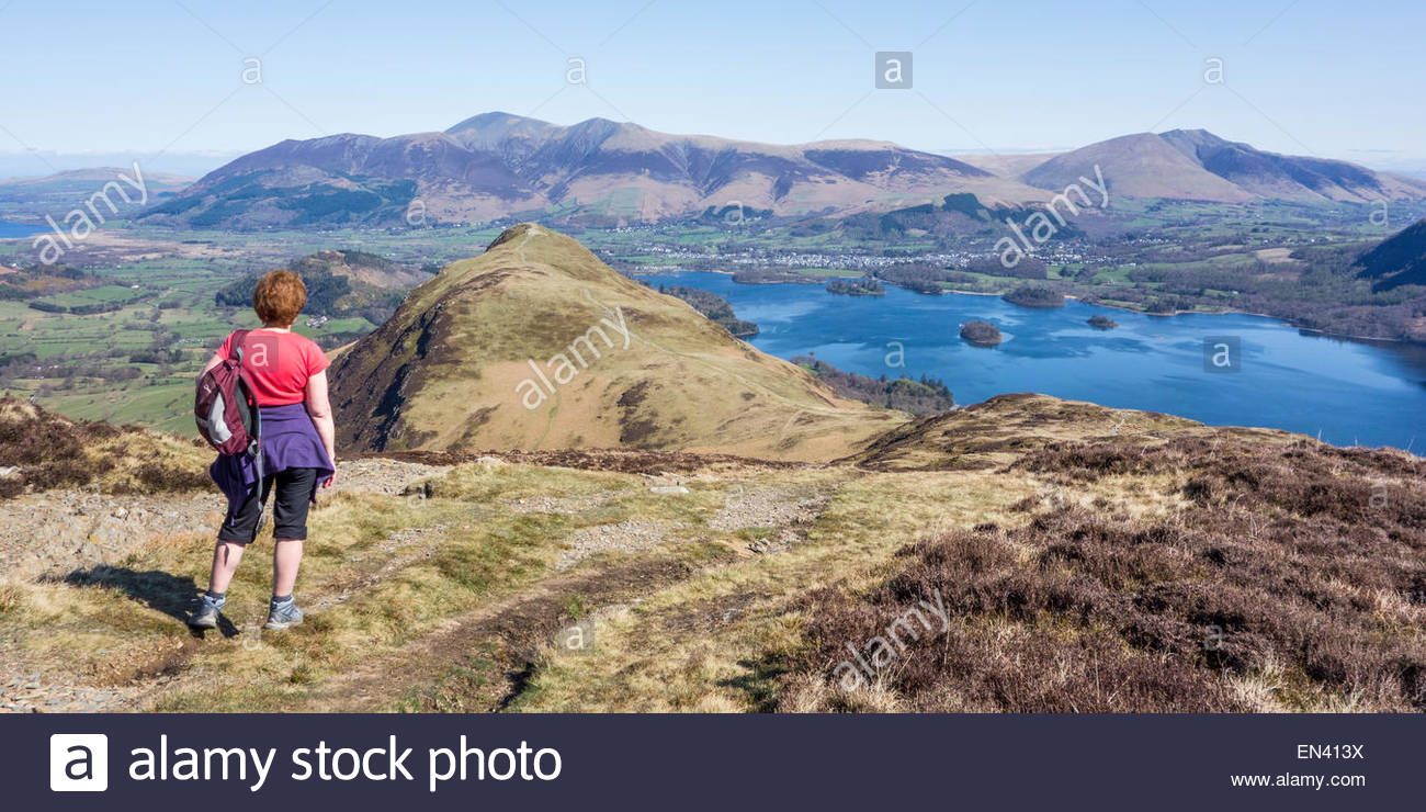 A walker pauses on the way up to Maiden Moor to take in the view of Catbells, Derwentwater and the distant Lake - Stock Image