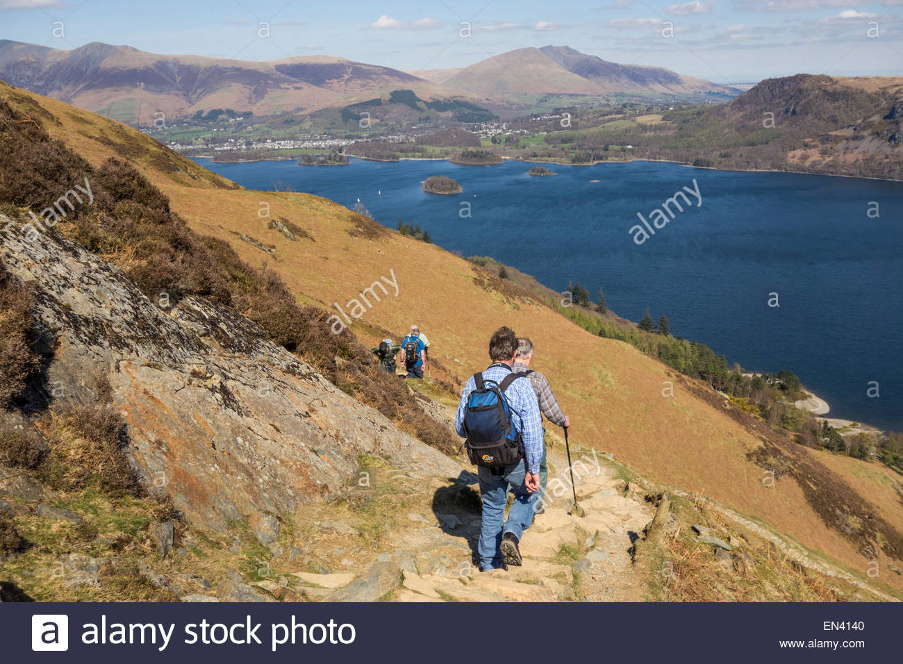 Walkers descending a steep rocky path on the way down off Catbells in the Lake District, with Derwentwater and the - Stock Image