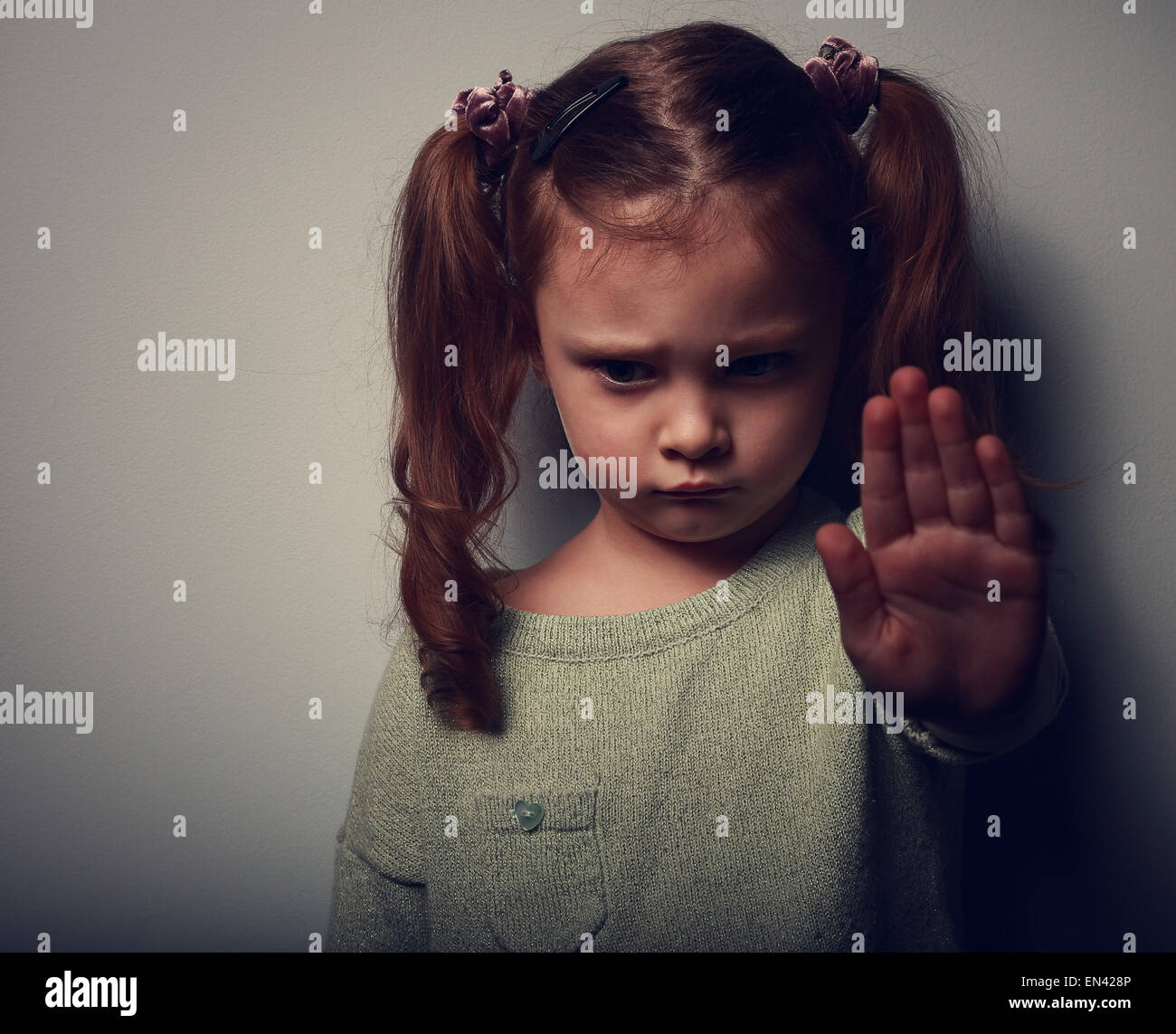 Kid girl showing hand signaling to stop violence and pain and looking down on dark background. Closeup color portrait - Stock Image