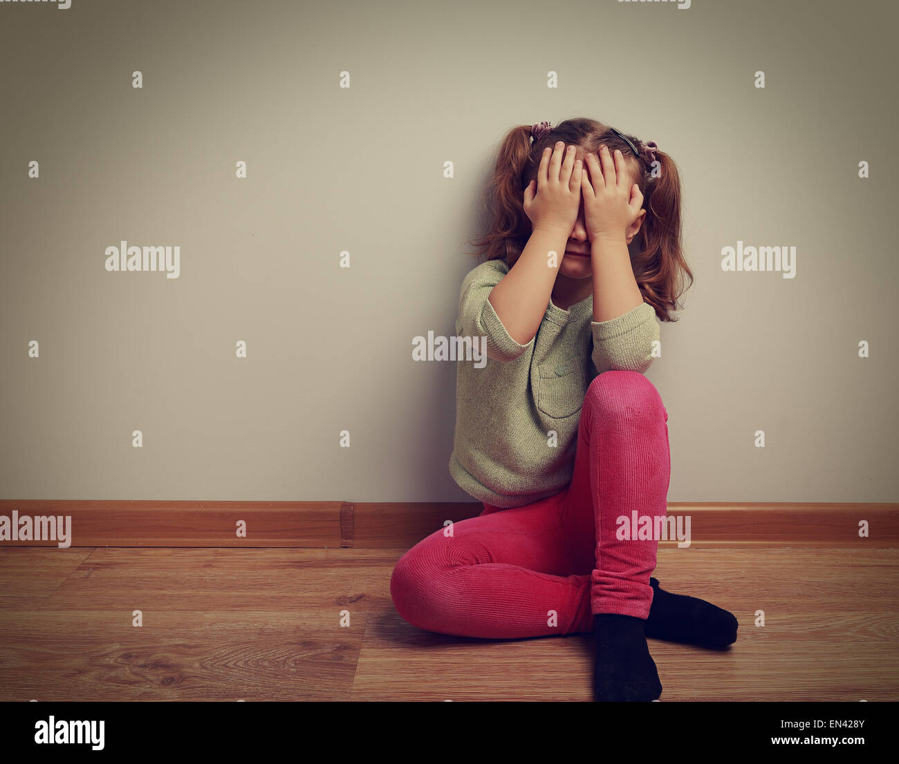 Frightened crying kid girl sitting on the floor with closed face the hands. Vintage closeup portrait - Stock Image