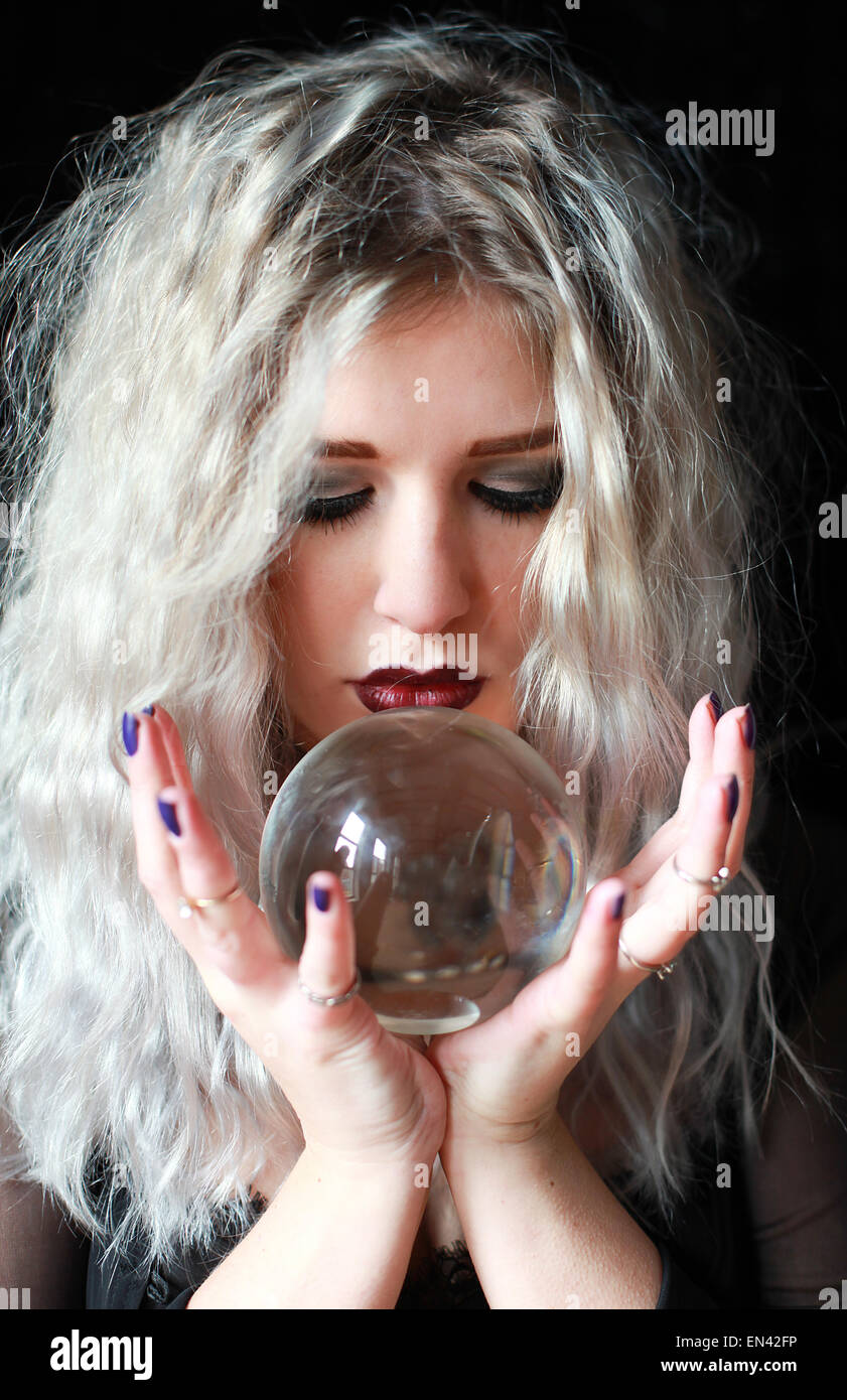 Beautiful young woman holding a crystal ball - Stock Image