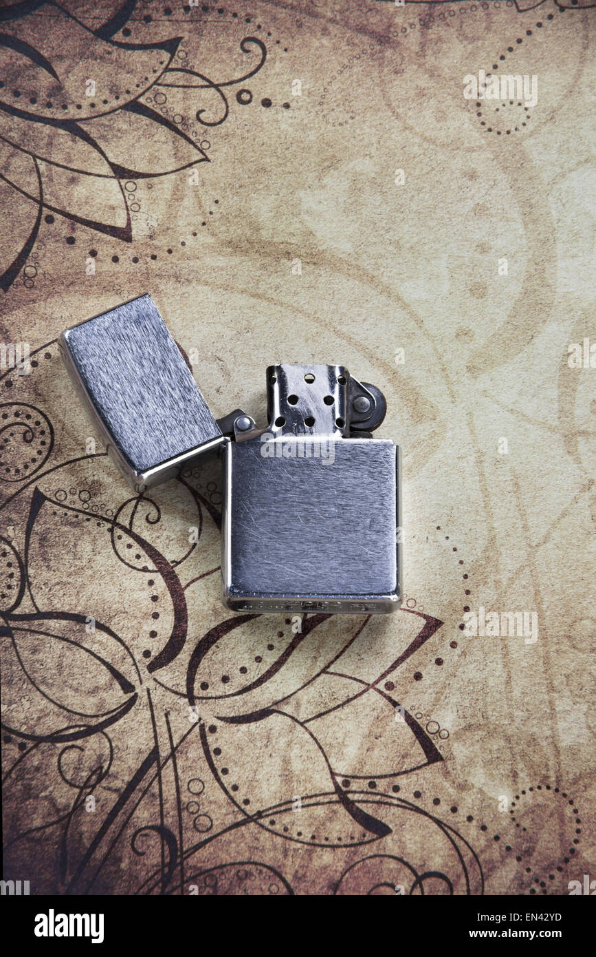 A Zippo lighter on a patterned background - Stock Image