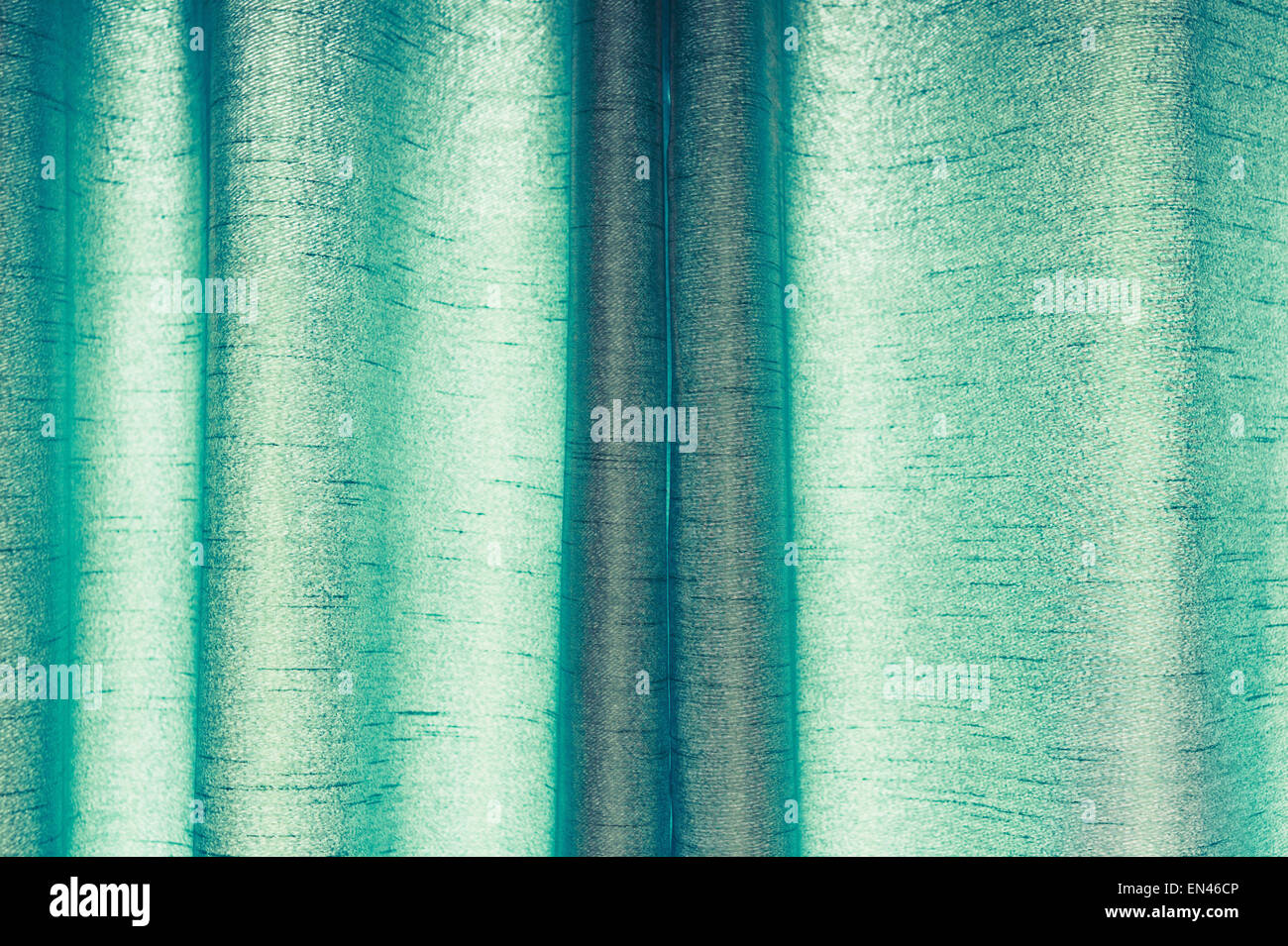 Part of a drawn pair of green curtains made from synthetic material Stock Photo