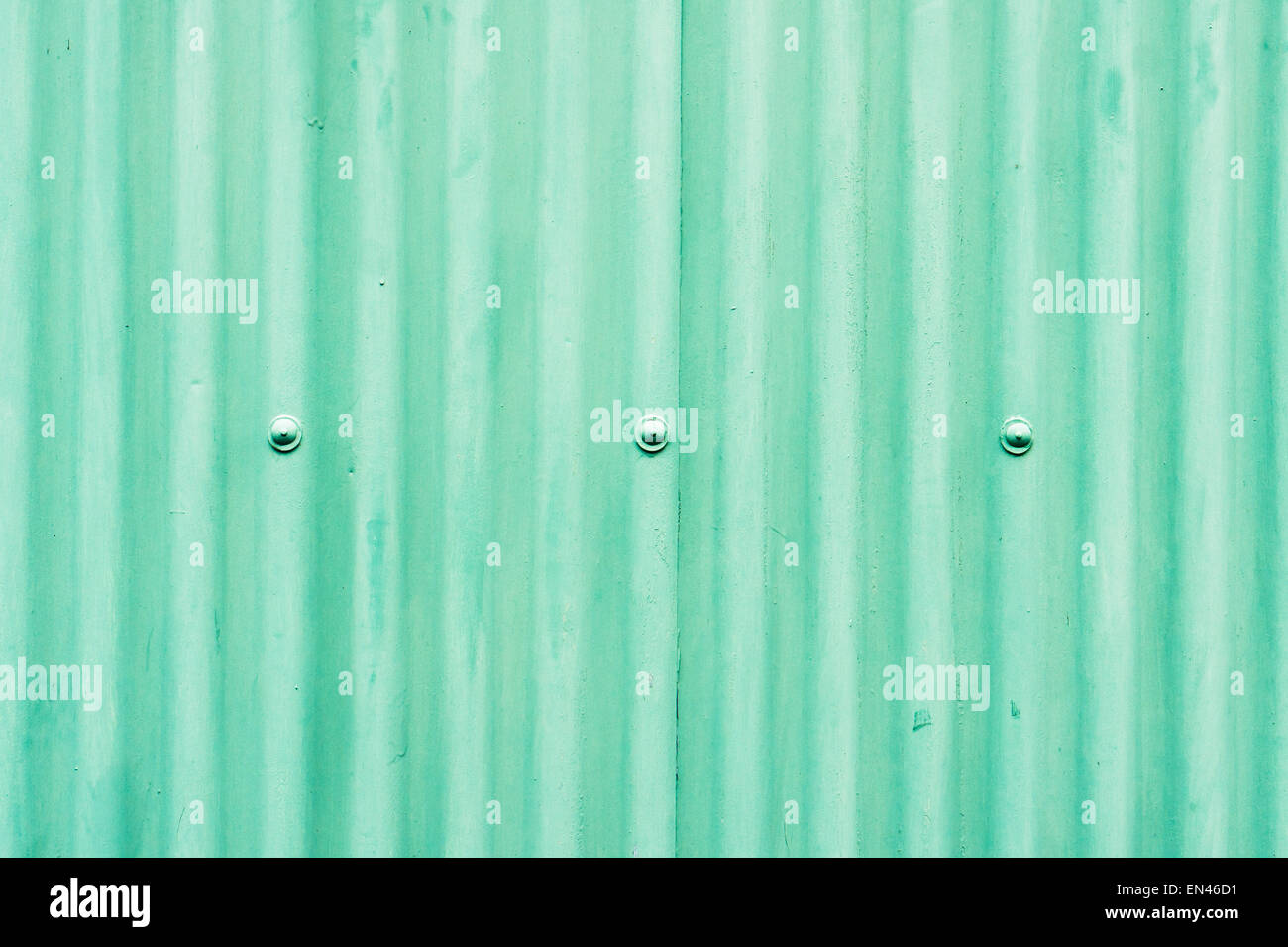 Part of a metal wall made from corrugated metal painted green Stock Photo