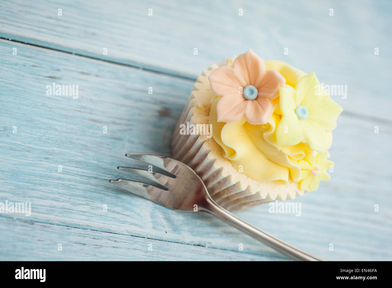 Yellow cupcakes on a wooden board - Stock Image
