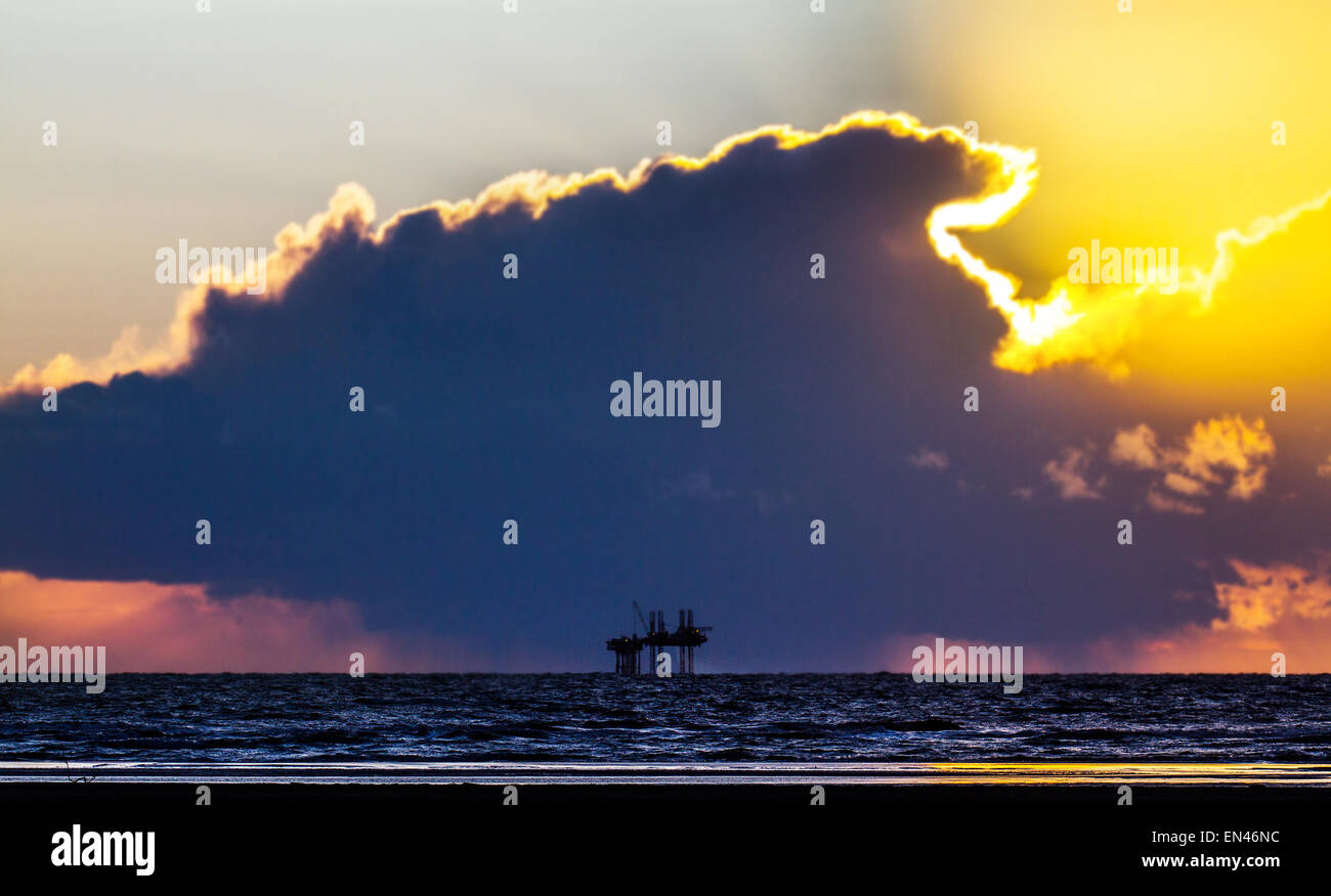 Ainsdale, Southport, Merseyside, UK. 27th April, 2015. UK Weather.  Colourful sunset over Morecambe Bay Gas Rig. - Stock Image