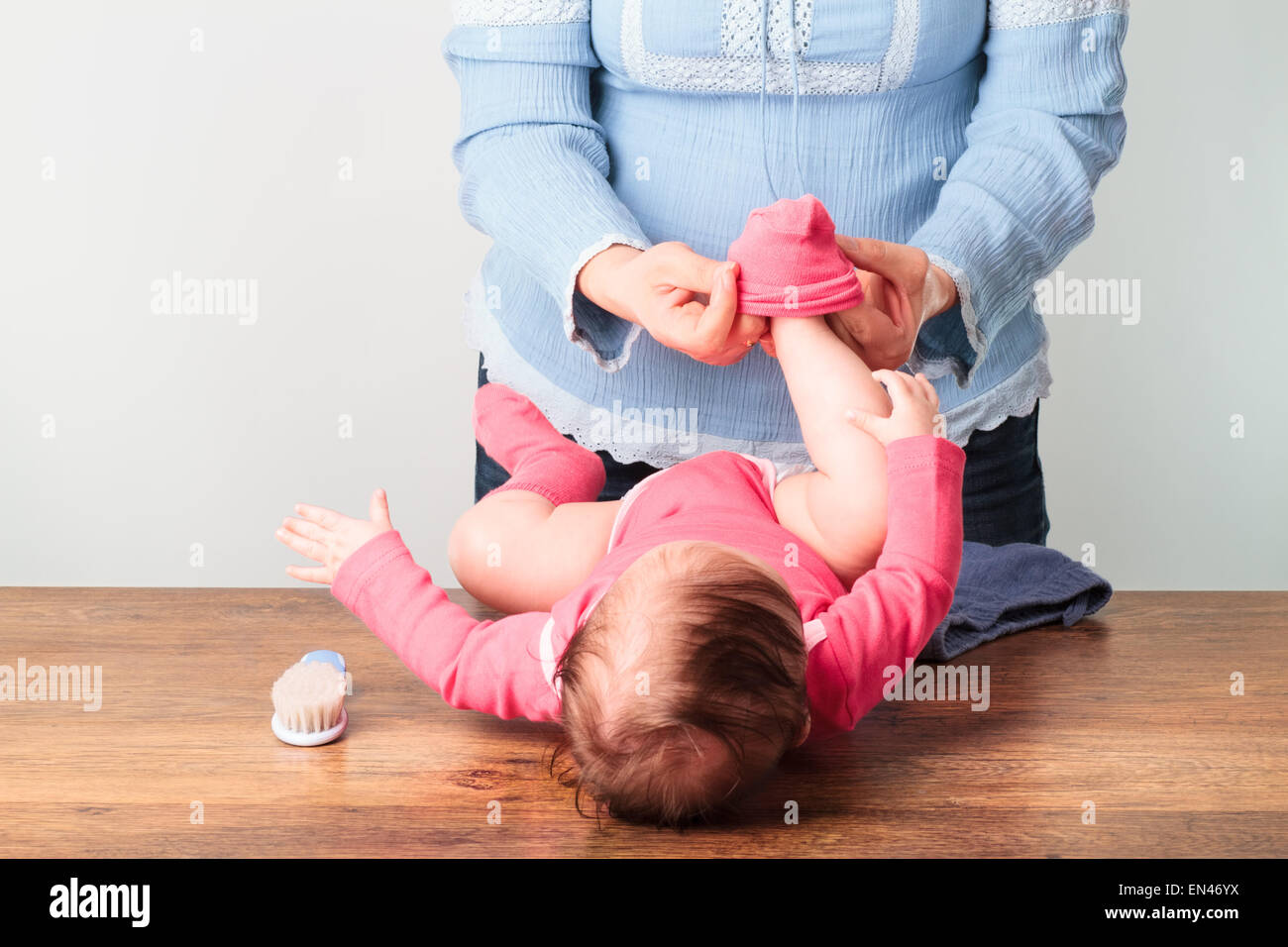 Mom putting on the socks her little baby girl - Stock Image