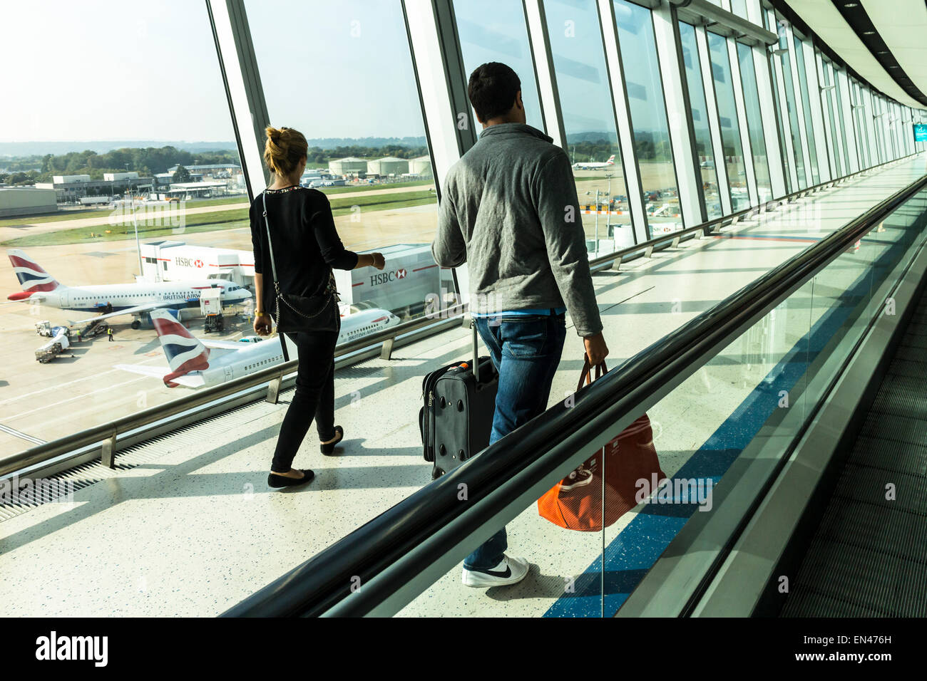 Passengers walking along the bridge from the hub to the North Terminal, Gatwick Airport, West Sussex, England. - Stock Image