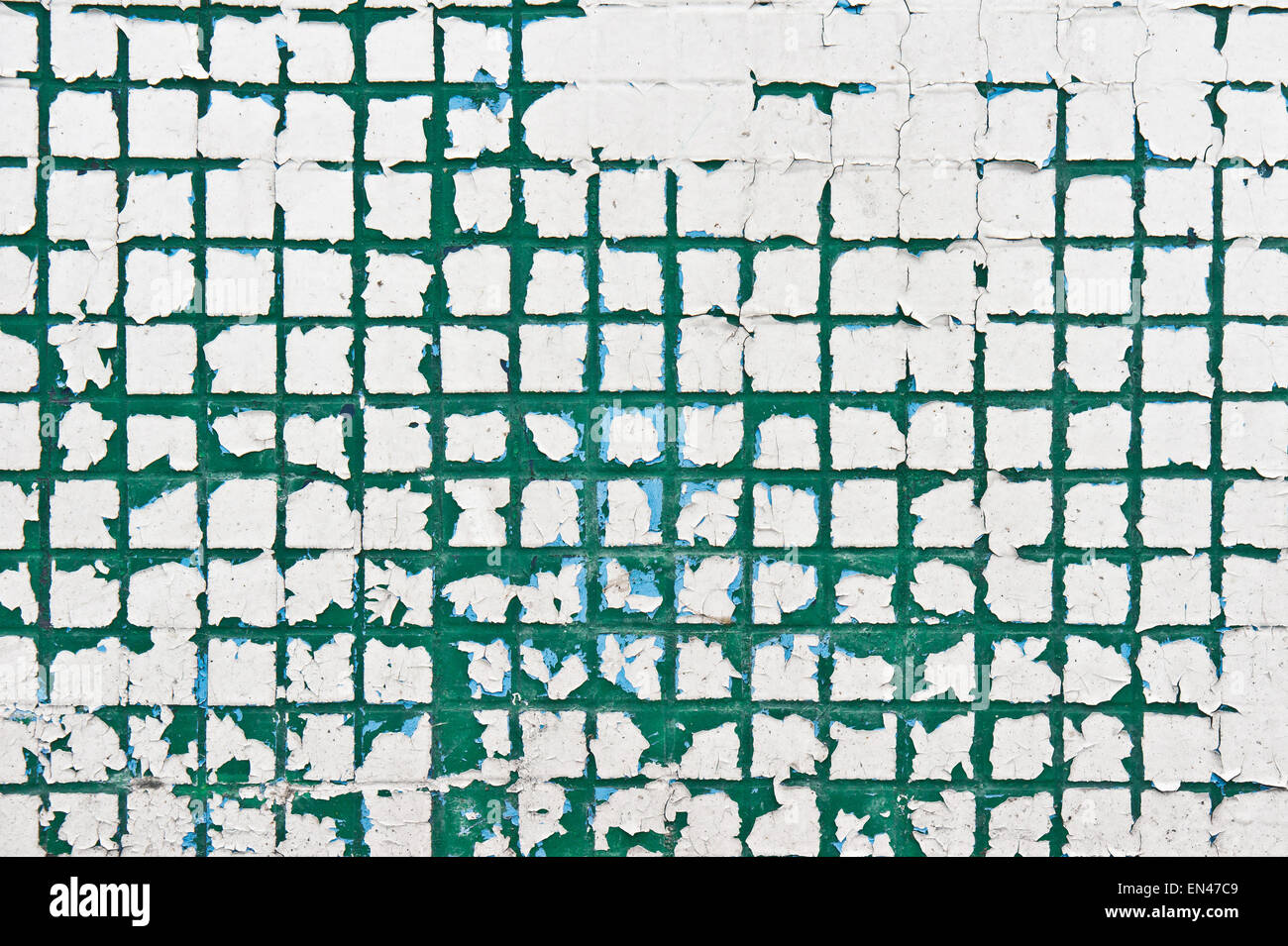 Peeling paint on a wall of tiles as a background image Stock Photo