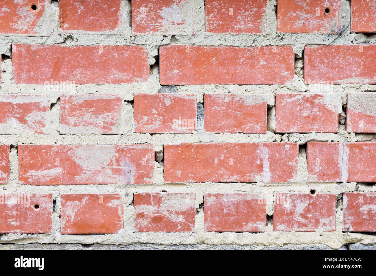 Messy cement in a brick wall Stock Photo