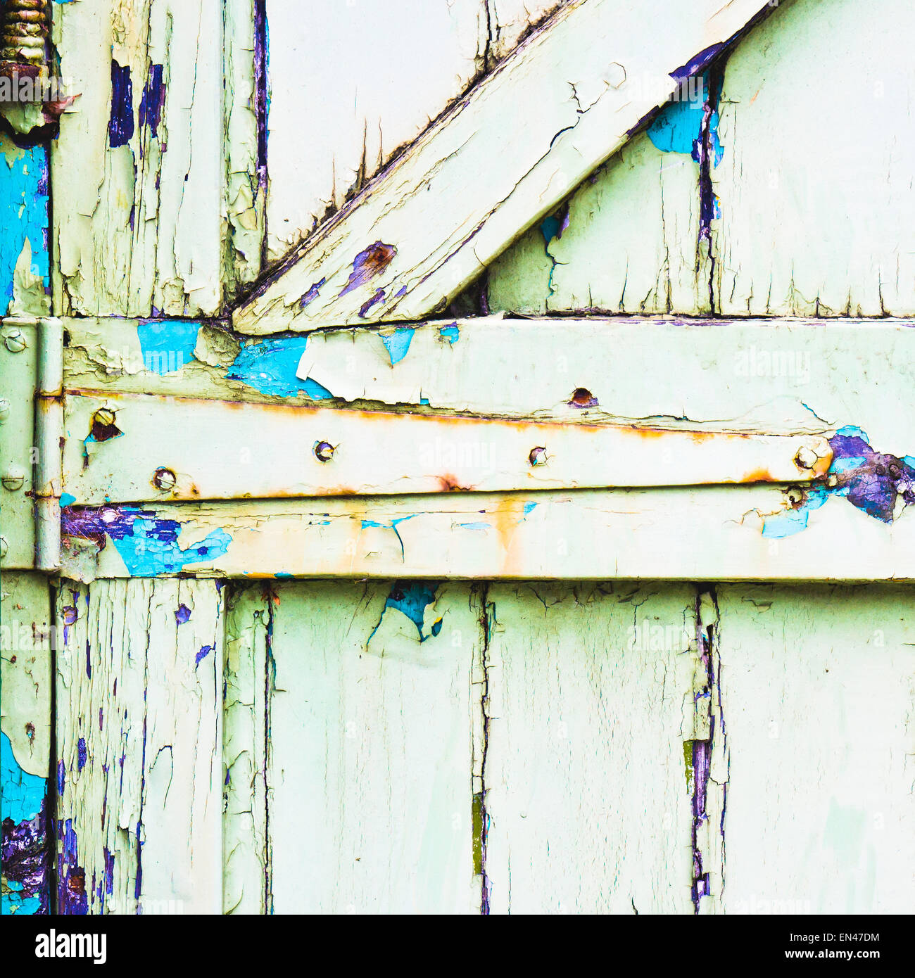 The hinge of a weathered green wooden gate Stock Photo