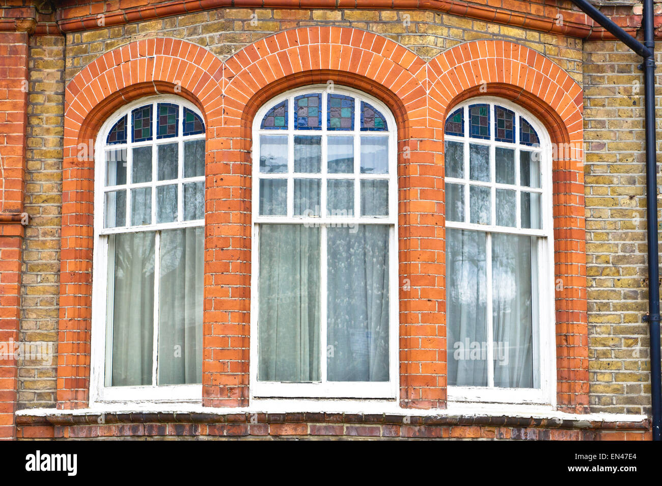 Arch windows in a red brick building in London, UK Stock Photo