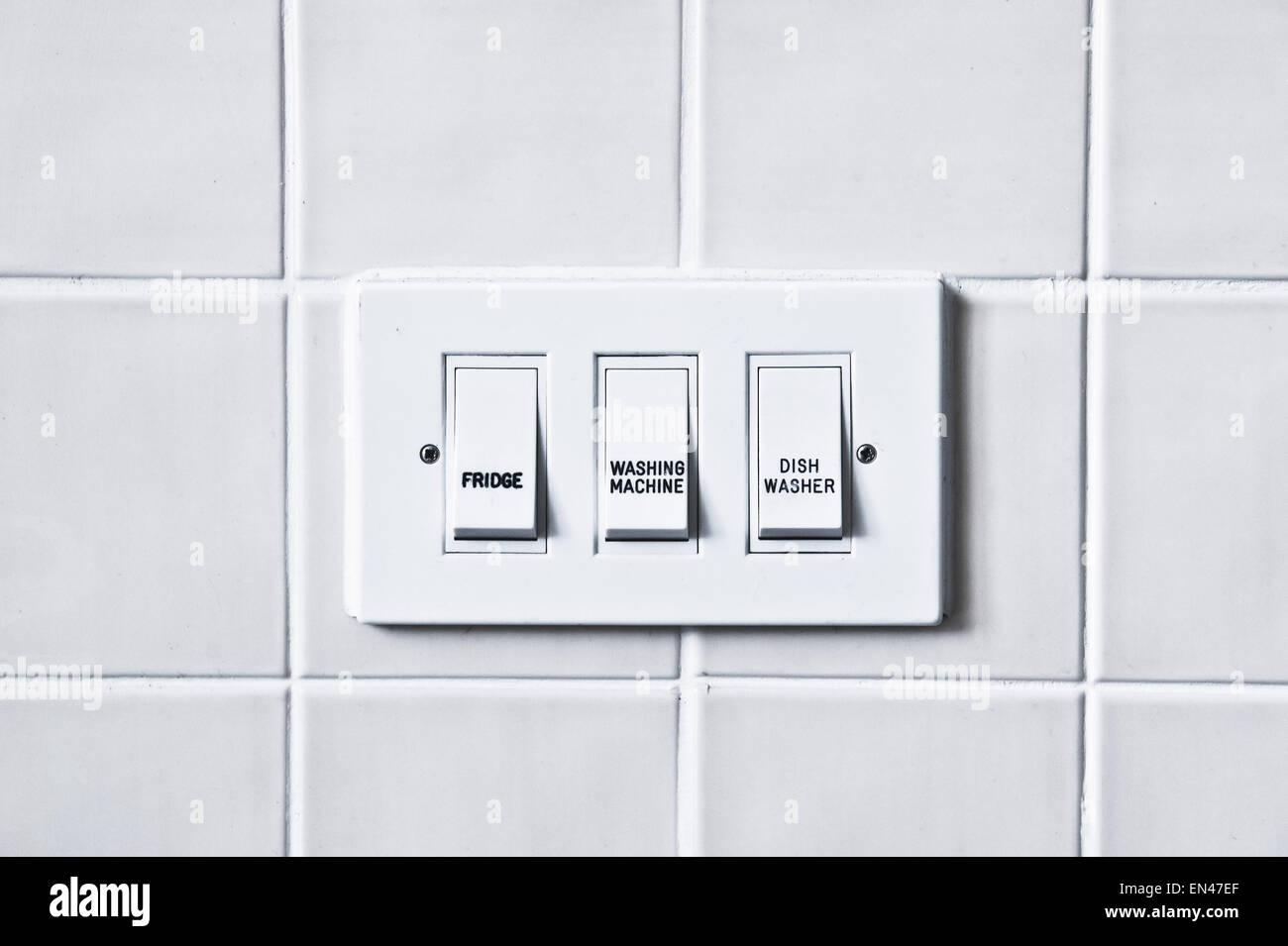 Switches for home appliances against a tiled wall Stock Photo