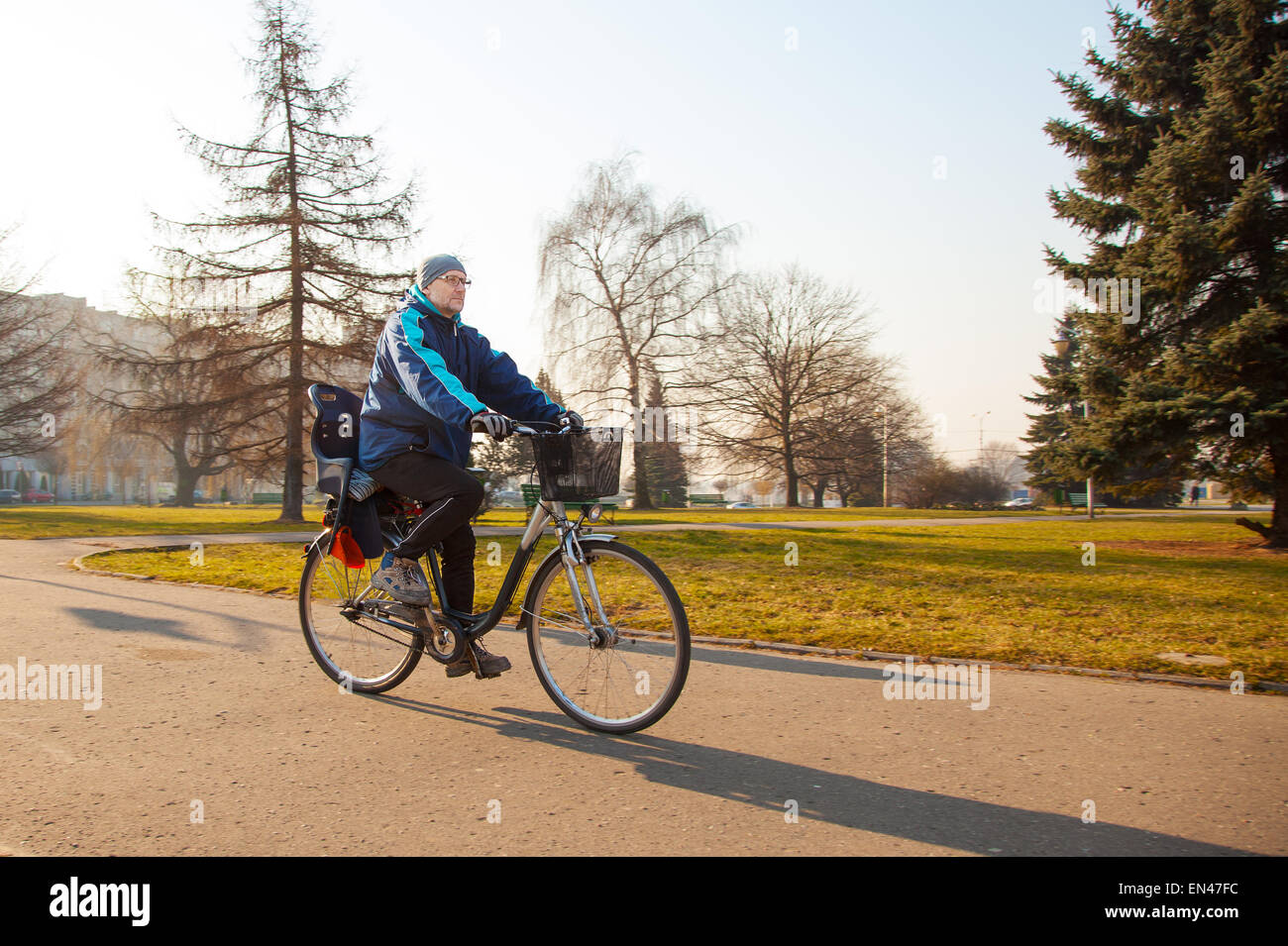 elderly man wearing glasses, a blue jacket, black trousers and a gray hat, riding a bike on the sidewalk Stock Photo