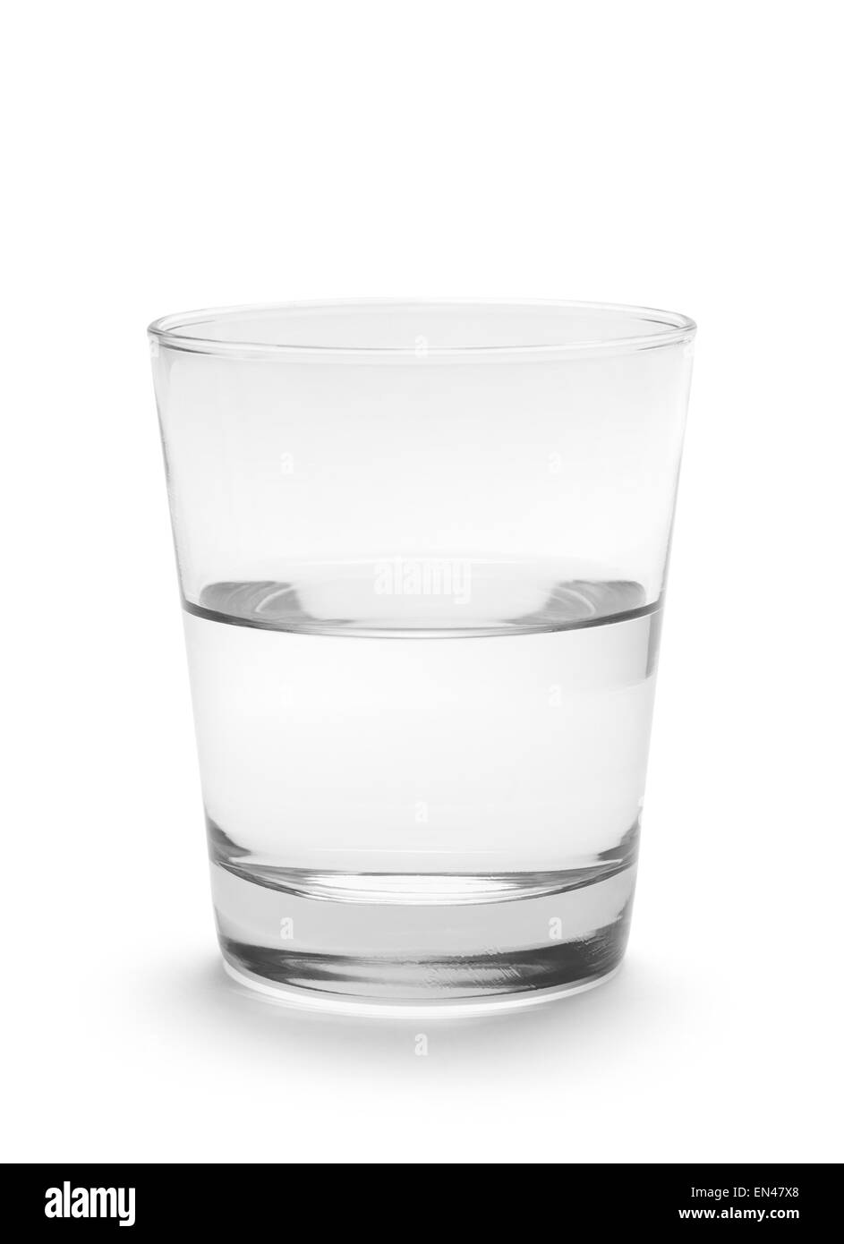 Small Glass of Water Half Full Isolated on White Background. - Stock Image
