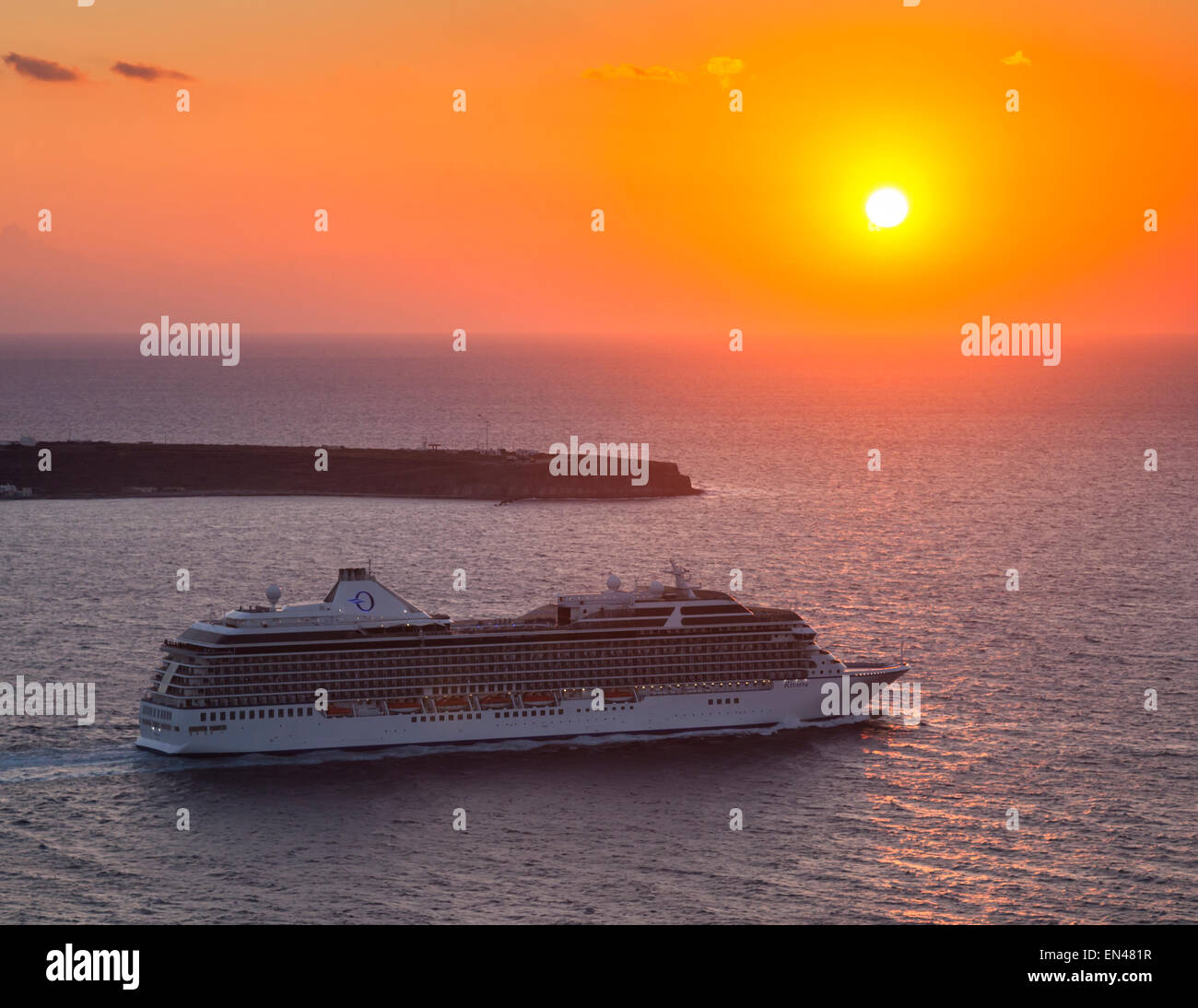 Cruise ship departing Santorini by the evening sunset headed for a new destination, Thera, Greece. - Stock Image